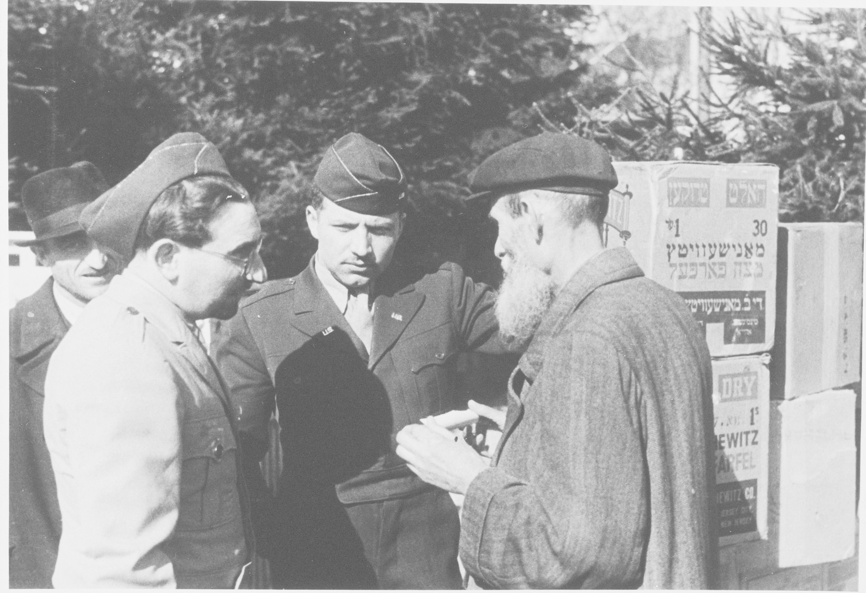 Rabbi Nathan Baruch and Rabbi Aviezer Burstein distribute Passover matza in an unidentified displaced persons' camp.