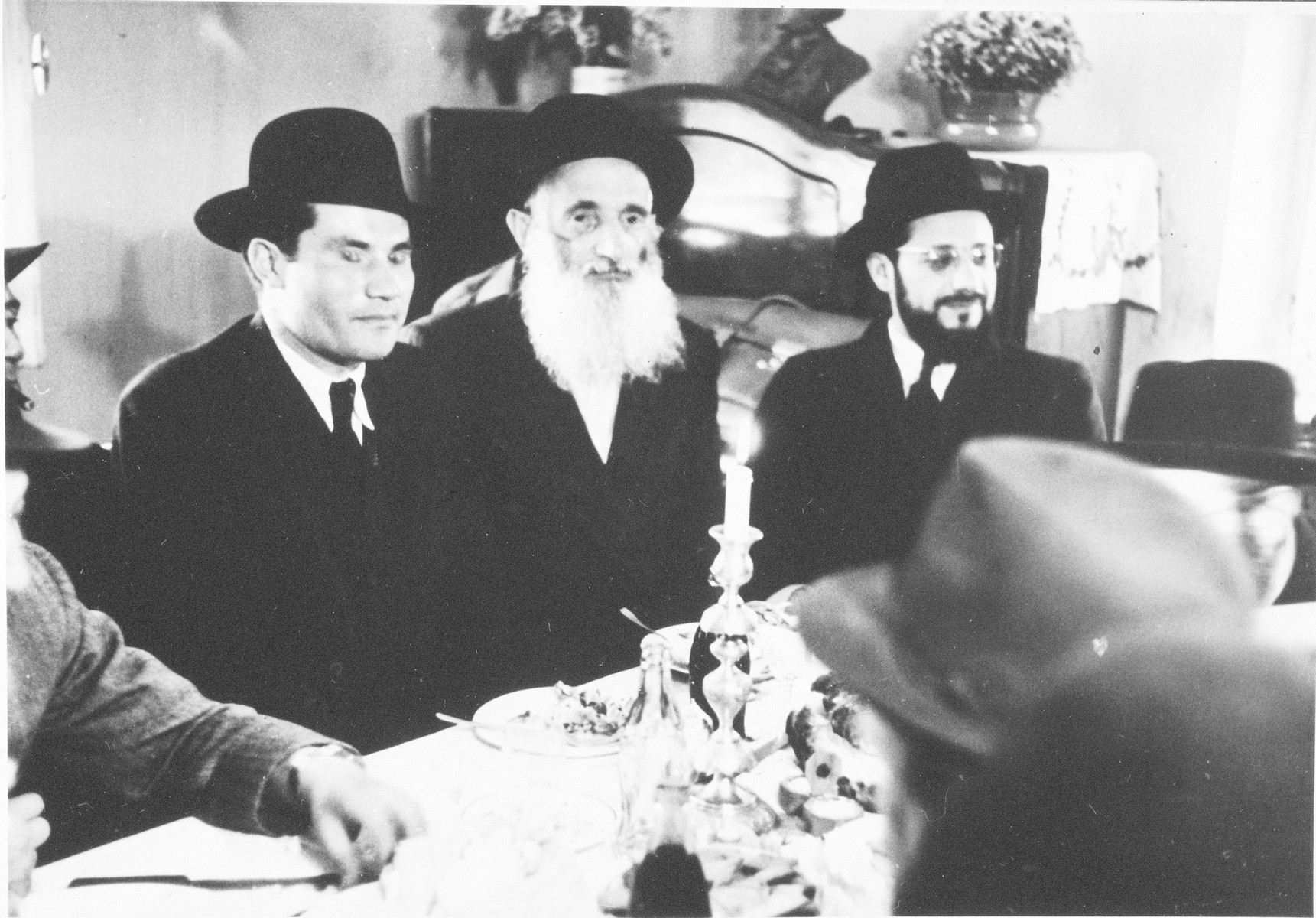 A group of Orthodox men gather around a festive table with candles in what [is probably the Zeilsheim displaced persons' camp].