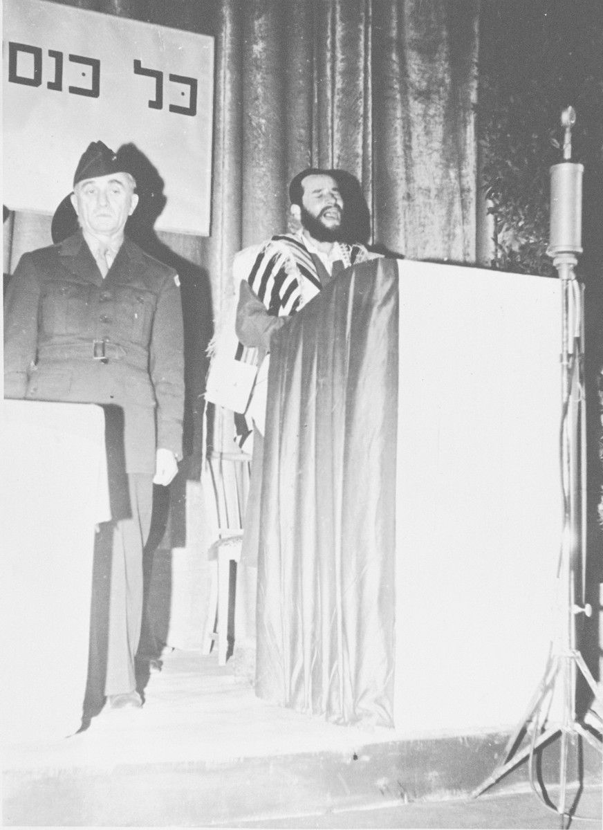 General Lucius Clay stands by a podium while Cantor Aaron Miller, draped in a prayer shawl sings at a religious convocation in an unnamed displaced persons' camp [possibly Fernwald].