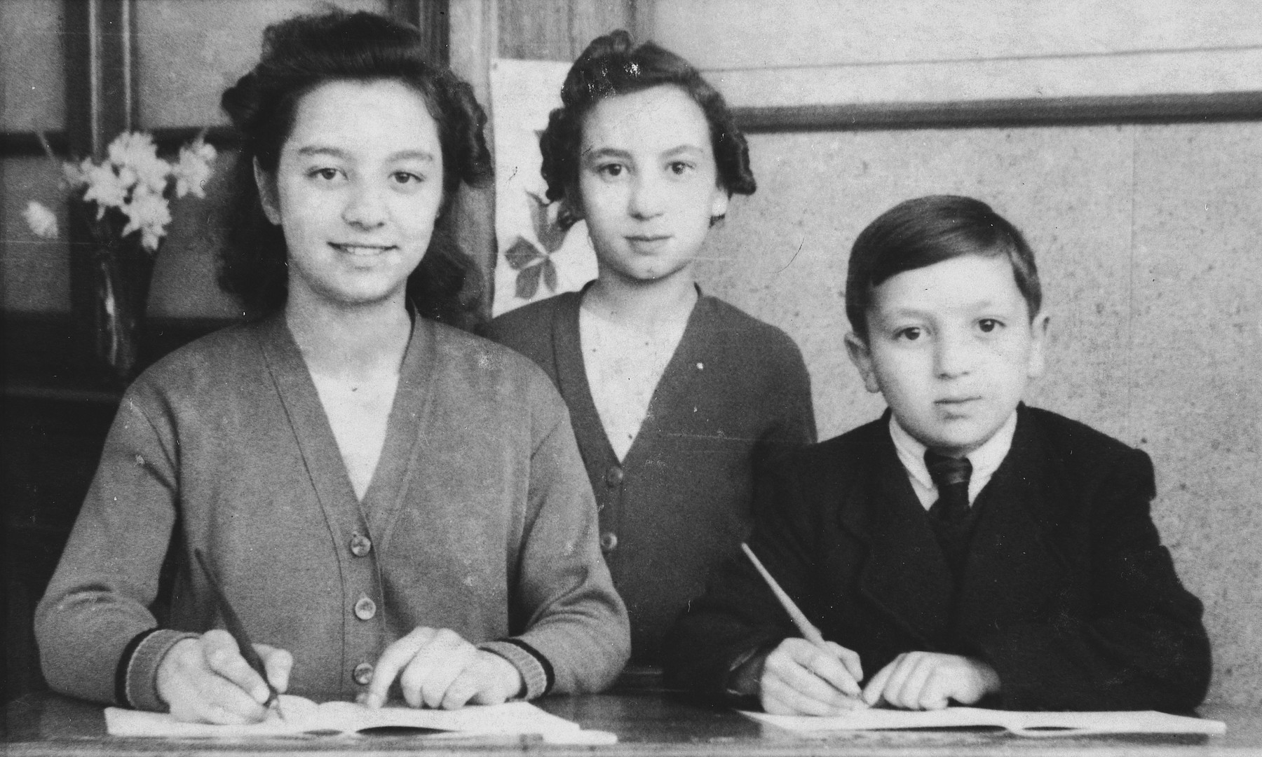Close-up portrait of three Belgian-Jewish siblings writing in their school books.  From left to right are Anny, Cecile and Charles Rojer.