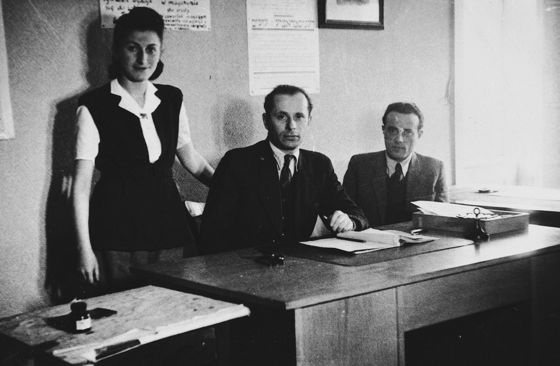 "Three employees of the Stuttgart displaced persons camp welfare department pose in their office.  Pictured from left to right are Dora Zajdenweber, R. Zylberberg, and I. Friedman.  One page from the Stuttgart Jewish DP camp album entitled, ""Jidiszer D.P. Center UNRRA--P.C.IRO in Stuttgart,"" compiled and photographed by Alexander Fiedel and dedicated to Moses Kornberg, head of the commissary."