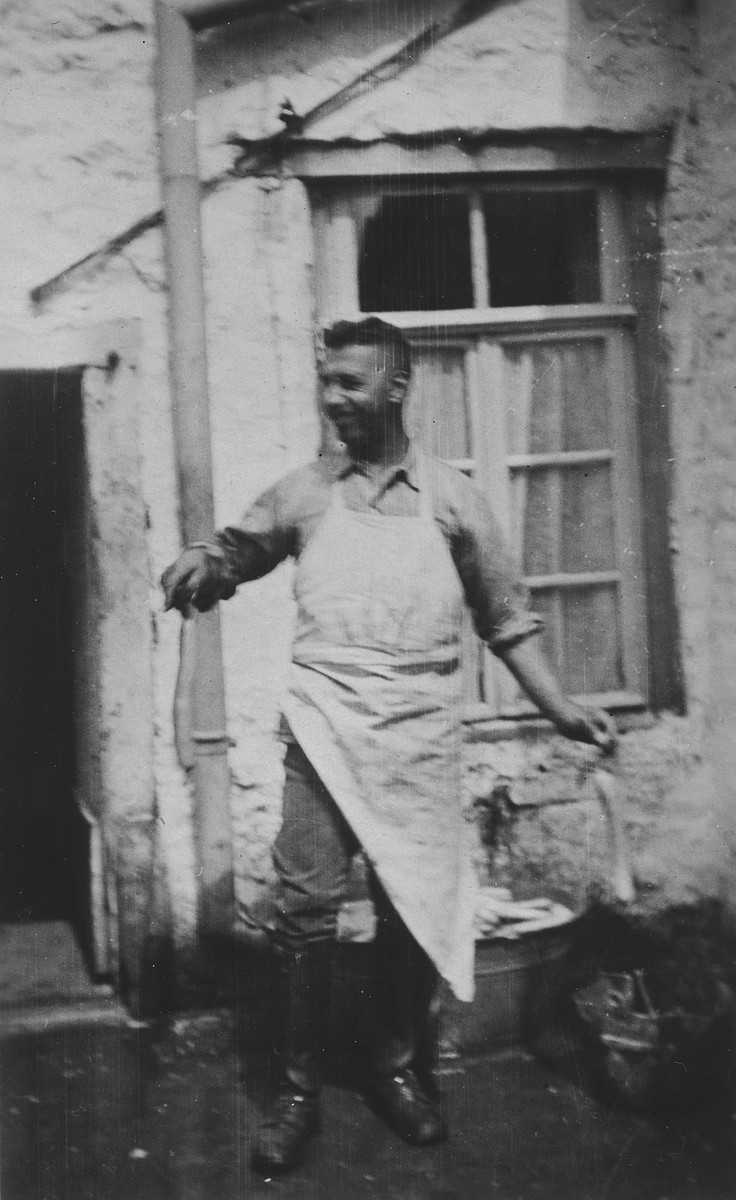 Hugo Pauly, a German-Jewish man wearing a large white apron, works in the family's butcher shop behind his home.