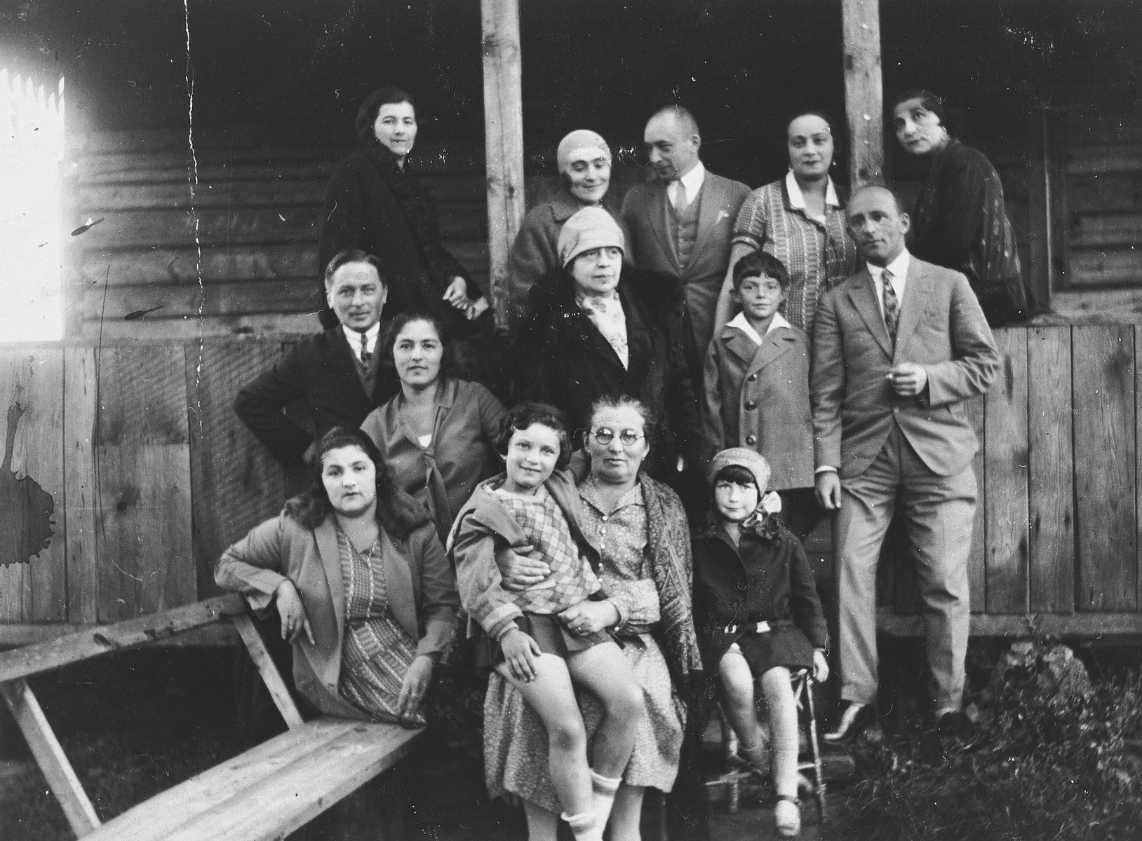 A Jewish family from Vilna gathers outside a wooden cottage for a group portrait while on vacation in Podbrodzie.  Pictured are the extended Zeldowicz family.  Emilia his sitting on the lap of her grandmother Sonja.