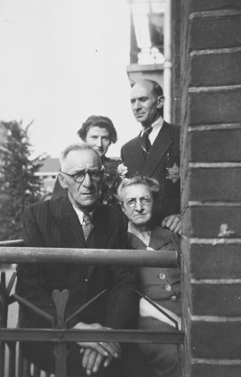 Members of the de Zwarte family pose on the balcony of their home wearing Jewish stars.  Pictured are Mietje, Simon and David de Zwarte (the grandparents and uncle of the donor) and David's girlfriend.  All were rounded up in 1943 and perished in concentration camp.