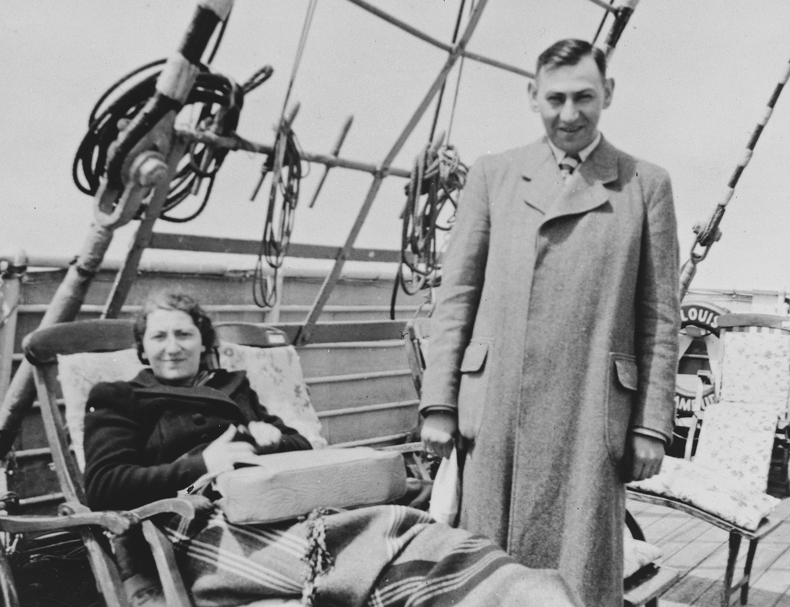 A female Jewish refugee relaxes on a deck chair while her husband stands next to her on the upper deck of the St. Louis.  Pictured are Ilse and Kurt Marcus.
