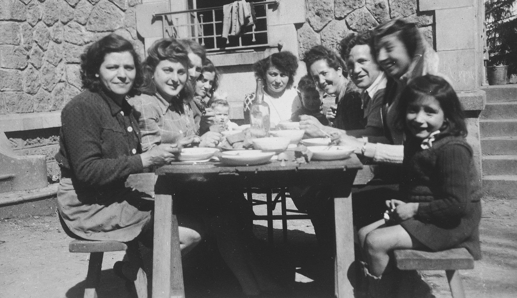 Jewish girls and teenagers eat outside in a courtyard in a postwar children's home in Feneyrols, France.