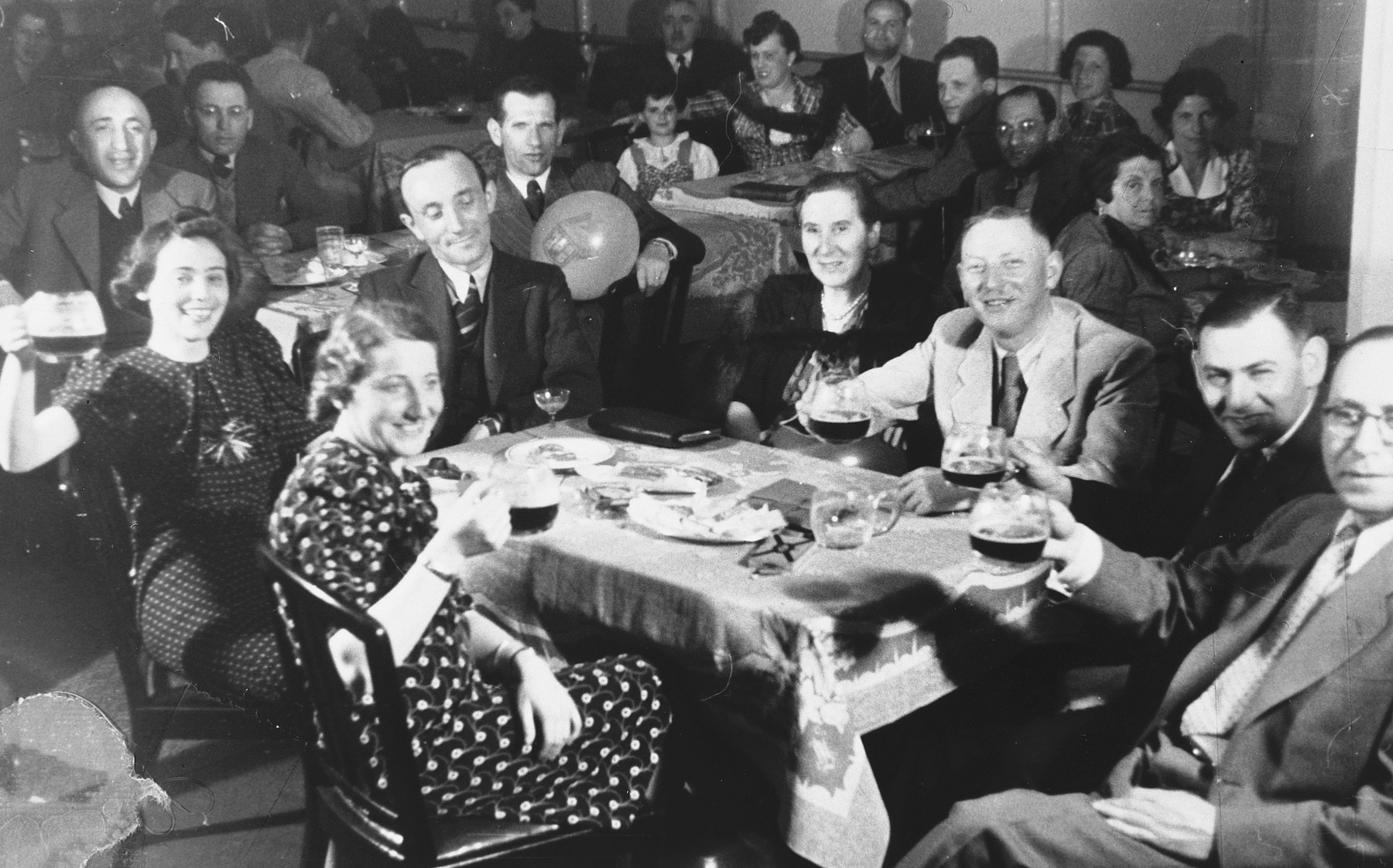 Jewish refugees on board the St. Louis raise their glasses in a toast.  Pictured are Ilse Marcus (front center), her husband Kurt Marcus (second from right) and parents, Berthold and Elfriede Meyer facing her.