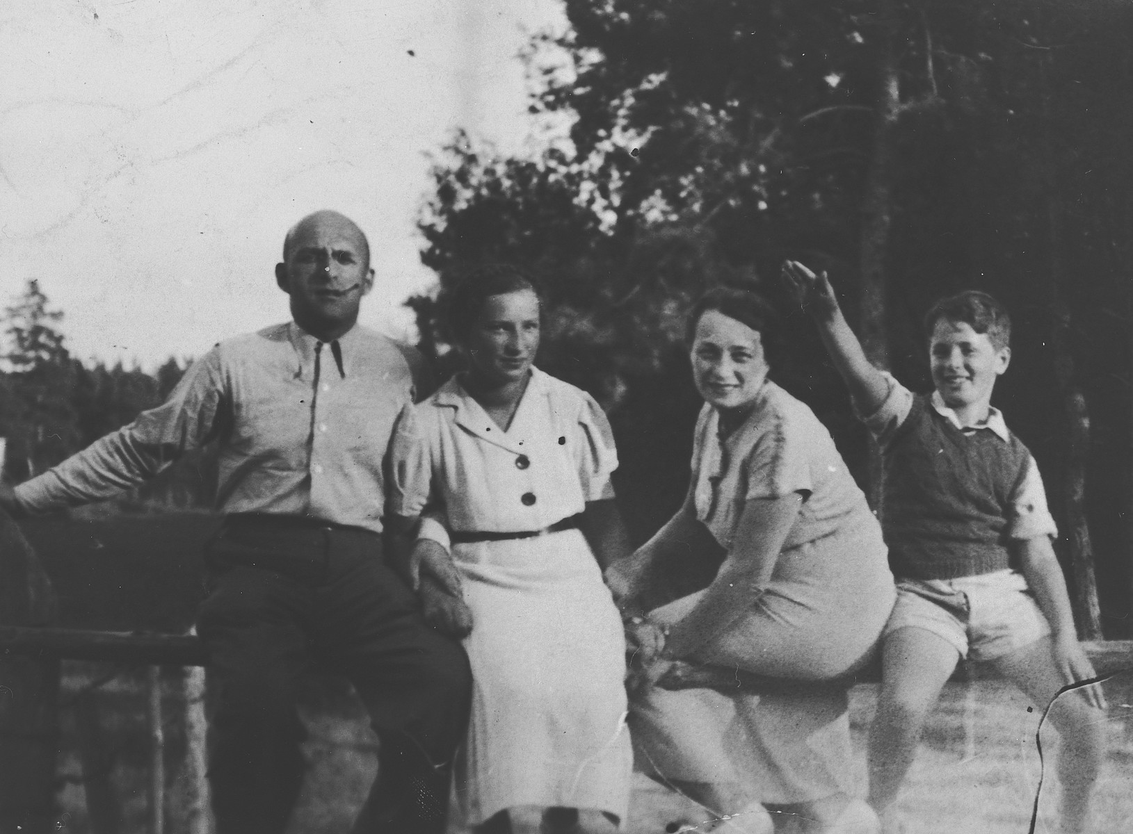 A Jewish family from Vilna sits on a railing while on an outing.  Pictured from lef tto right are David, Emilia, and Henrietta Zeldowicz and Alik Abramowicz.  Arik Abramowicz perished during the Holocaust.