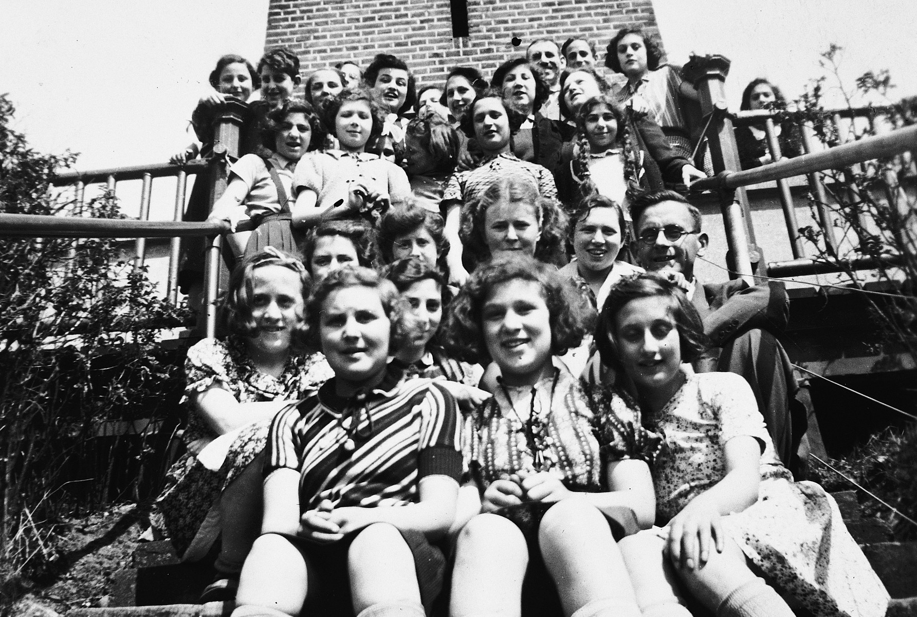 Group portrait of German-Jewish children sitting on the steps of the Ons Boschhious children's home in Driebergen.