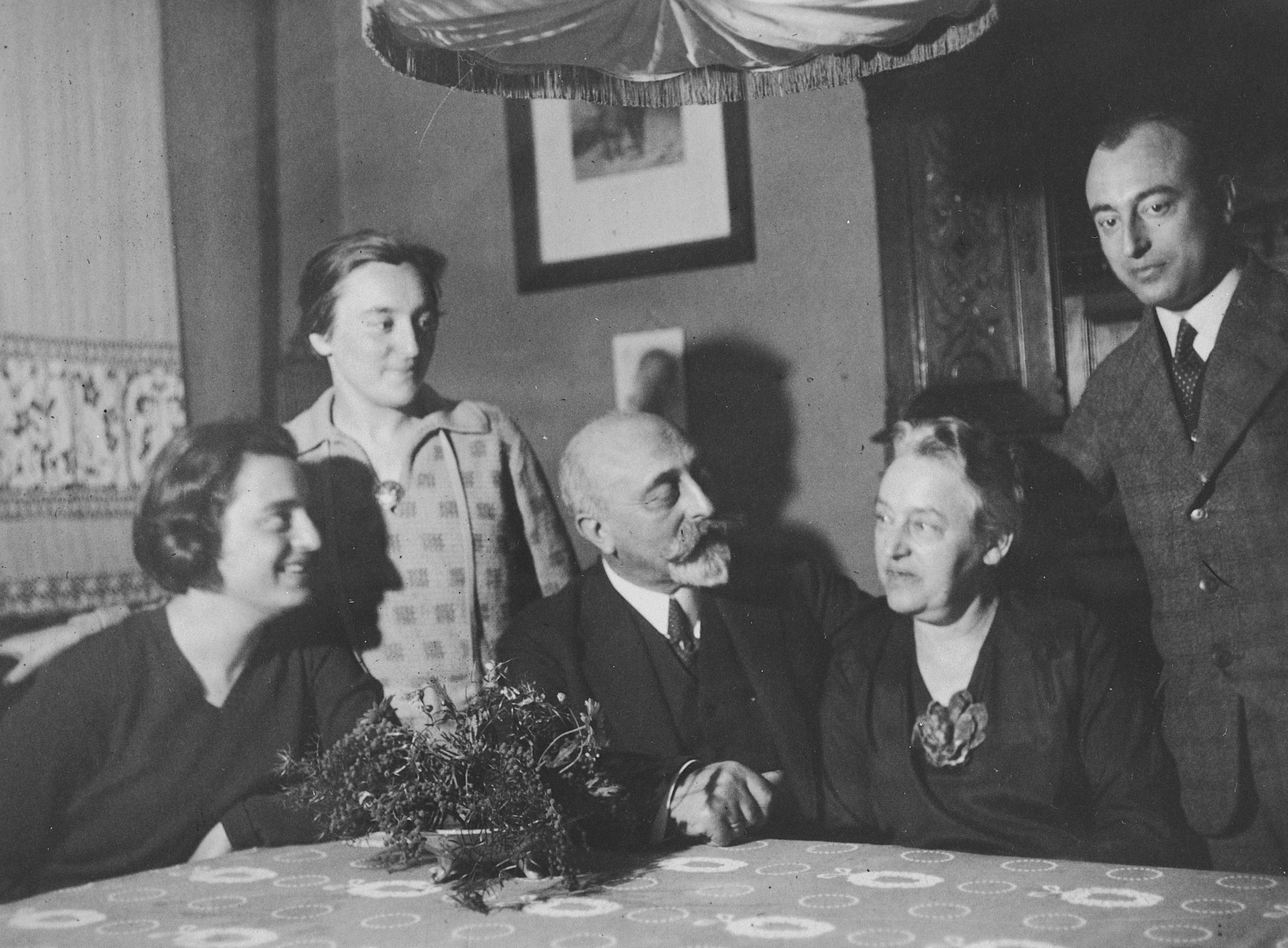 An elderly German-Jewish couple sits at their table holding hands, surrounded by their three children.  Pictured in the center are Leopold Herz and his wife Lena Solomon Herz.  Also pictured are their children, Richard, Lotte and Lilly.