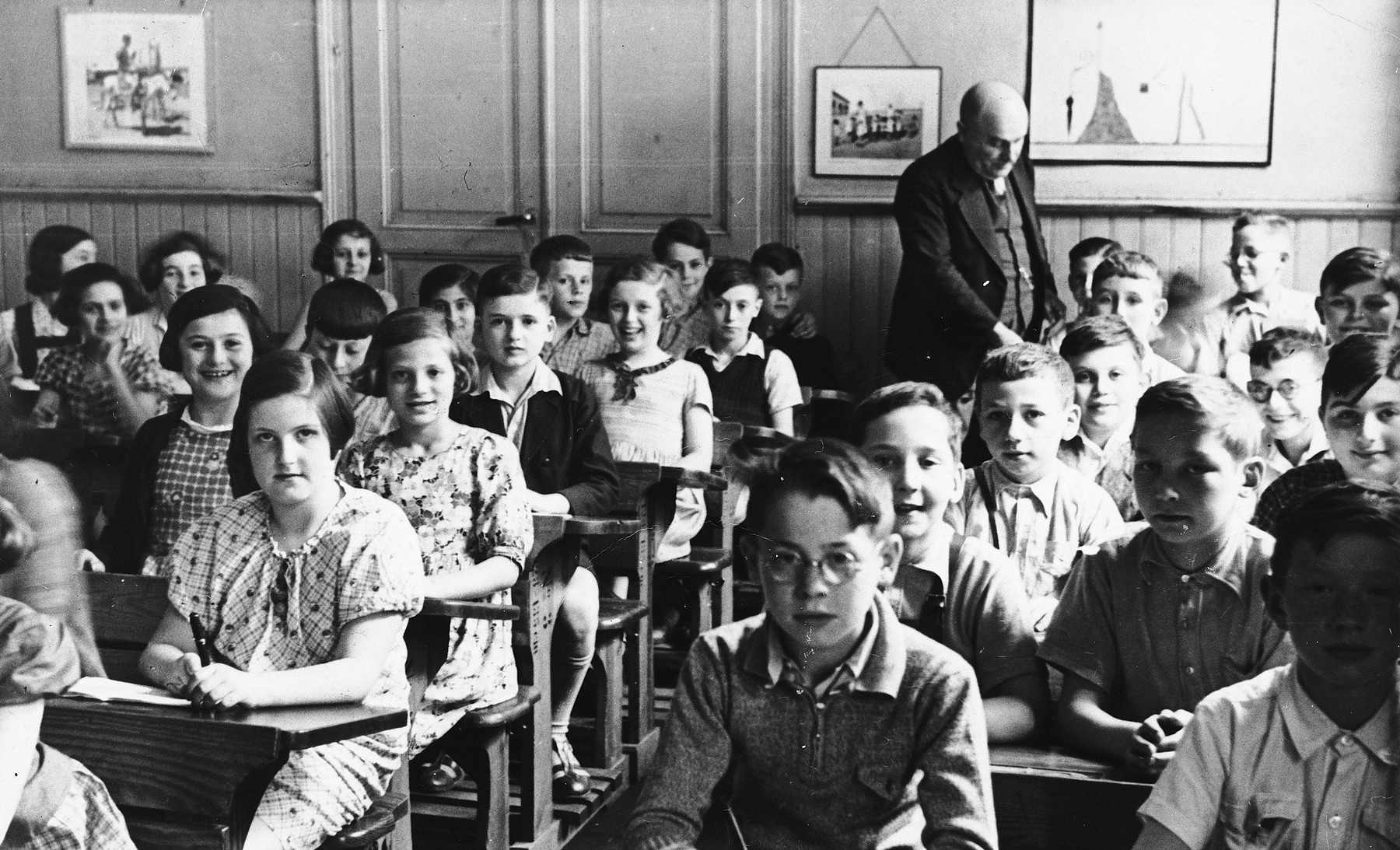 Elementary school students sit at their desks in a classroom in Kassel, Germany.  This photograph was sent to Bertha Meyer while she was on a Kindertransport in Holland by a former classmate from Bertha's school in Kassel, Germany.