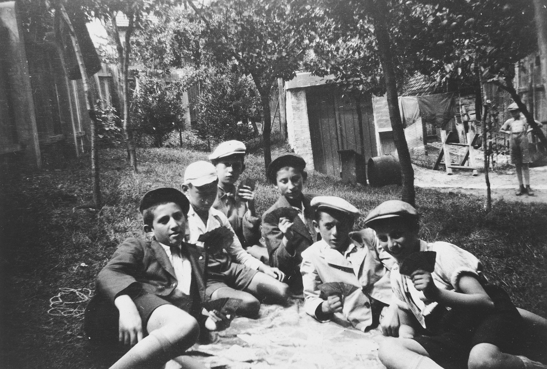 Boys in an Orthodox summer camp in Hungary play a game of cards on the lawn.
