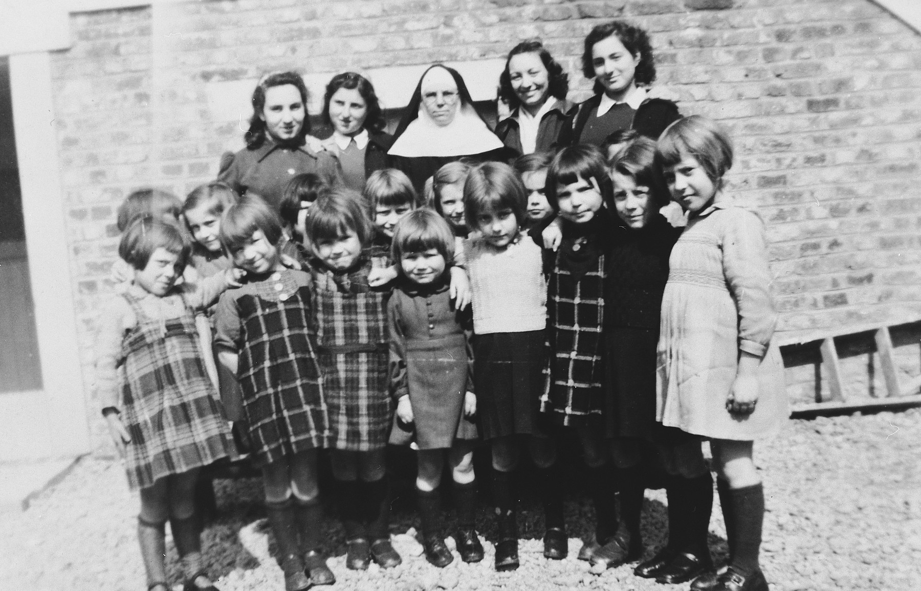 Two Jewish sisters pose with the nun who had hidden them and a group of Belgian children in the Couvent de la Misericorde in Louvain.  Pictured in the back row are Cecile and Anny Rojer and Sister Clotilde.