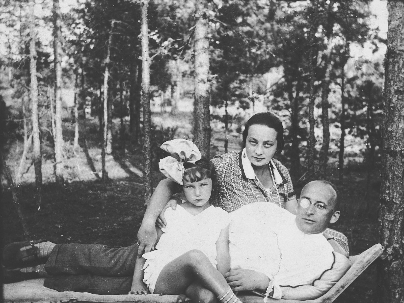 A Jewish family from Vilna poses on a lawn chair while on vacation in Podbrodzie.  Pictured are David, Henrietta, and Emilia Zeldowicz.