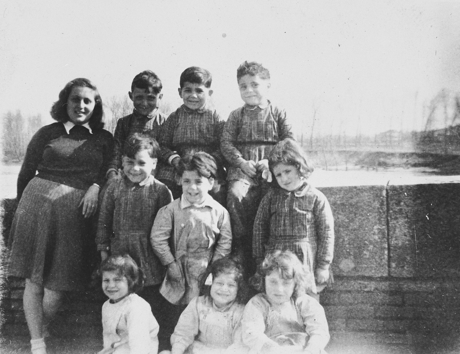 A Jewish teenager poses for a group portrait with the young children she is helping teach the alphabet to in Vic-sur-Cere.  Pictured standing on the left is the donor, Ruth Strauss.