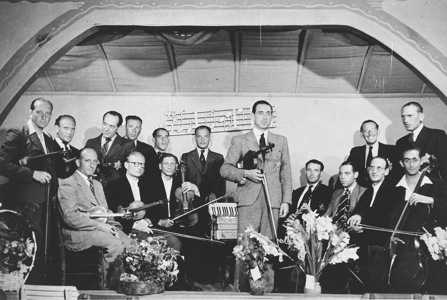 Members of the Westerbork string orchestra pose on stage with their instruments.  Guitarist  Salomon de Zwarte is standing third from the left.