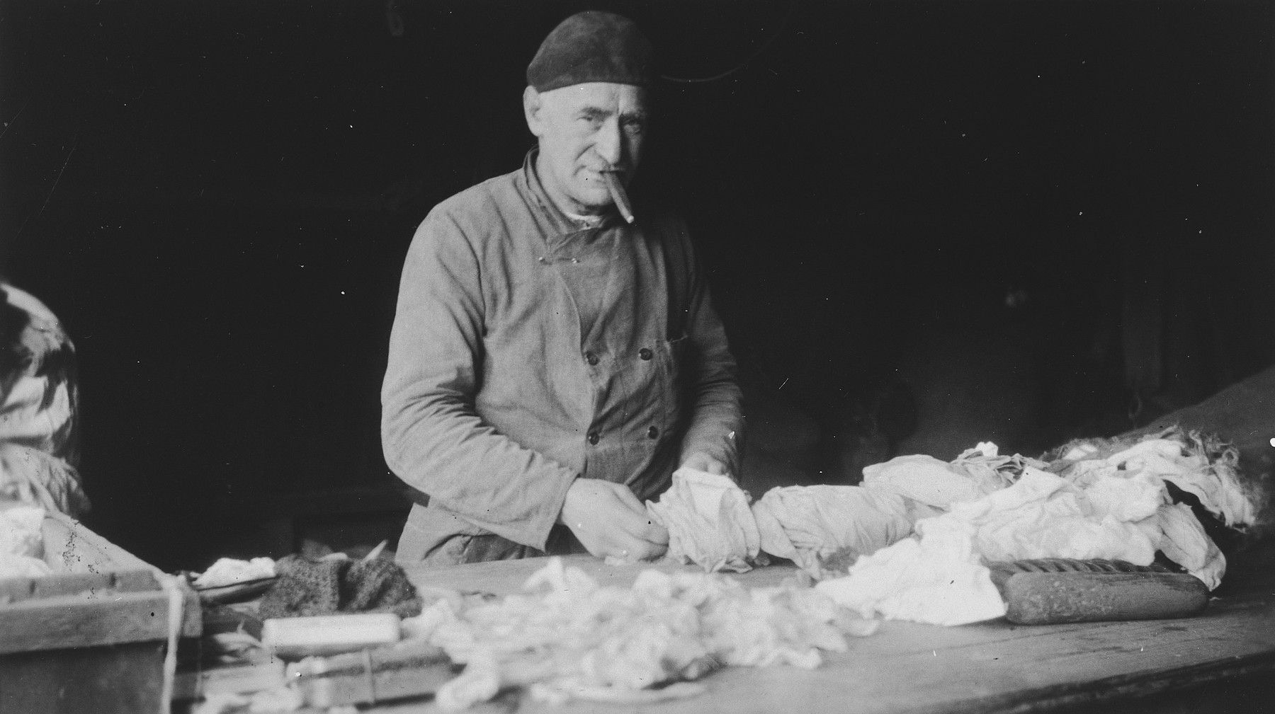 An elderly Jewish man sorts rags in a warehouse.    Pictured is Simon de Zwarte, grandfather of the donor.  He was rounded-up in 1943 and subsequently perished.  [The date is unconfirmed and this may be a prewar photograph.]