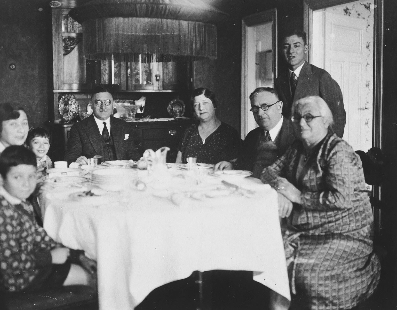 A Lithuanian Jewish family gathers around their dining room family.  Dr. Elias Sedlis sits at the head of the table.  To his right are his wife Anna and two sons, Alexander and Gabriel.  To his left is his sister Miriam, her husband, and his mother Shayne.  David Cukierman is standing.