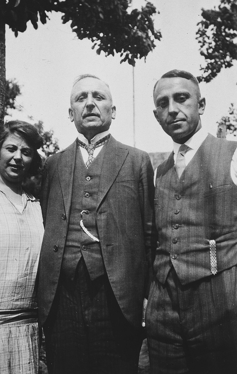 A German-Jewish father poses for a photograph with his daughter and son on either side.  From left to right are Selma, Levi (Lewis) and Alfred Herz.