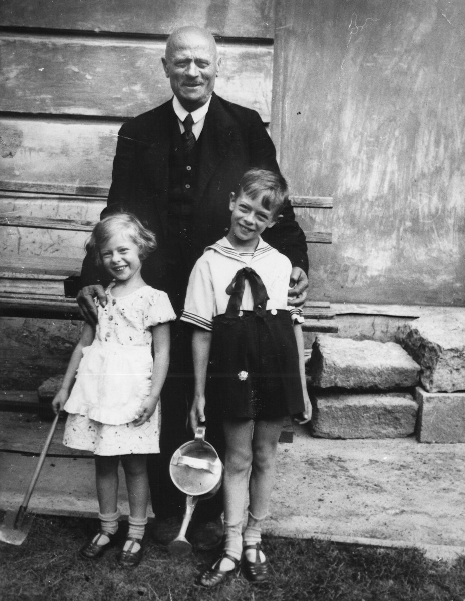 Olek and Irena Czoban stand in front of their [grand]father holding gardening equipment.