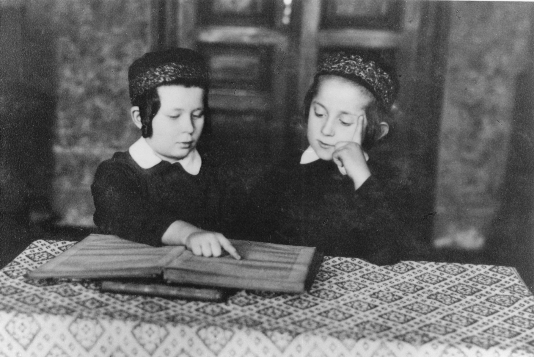 Two young Jewish Hasidic boys study a religious text while seated at a table.  Pictured on the right is Menahem-Mendel Horowitz, the seven-year-old son of Rabbi Tuvia Horowitz.