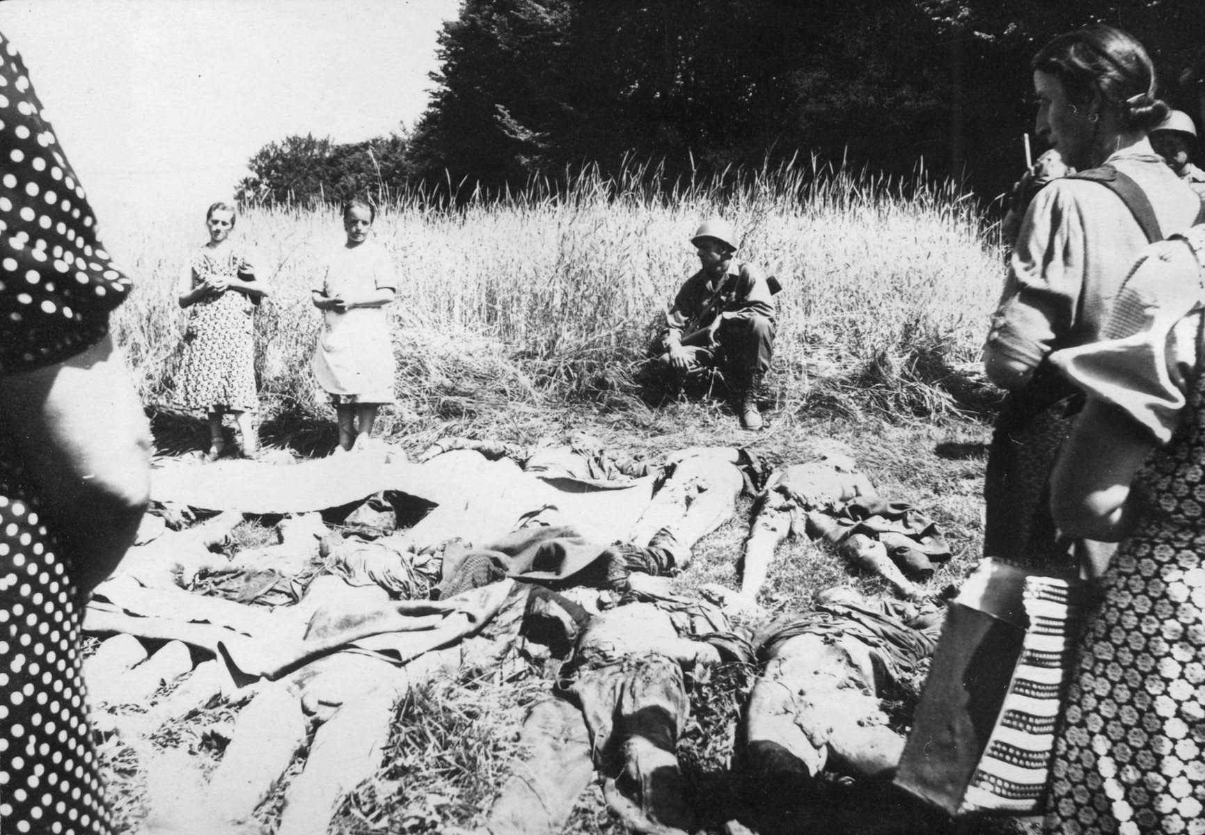 Female German civilians from Nammering are forced to view the corpses of prisoners exhumed from a mass grave near the town.