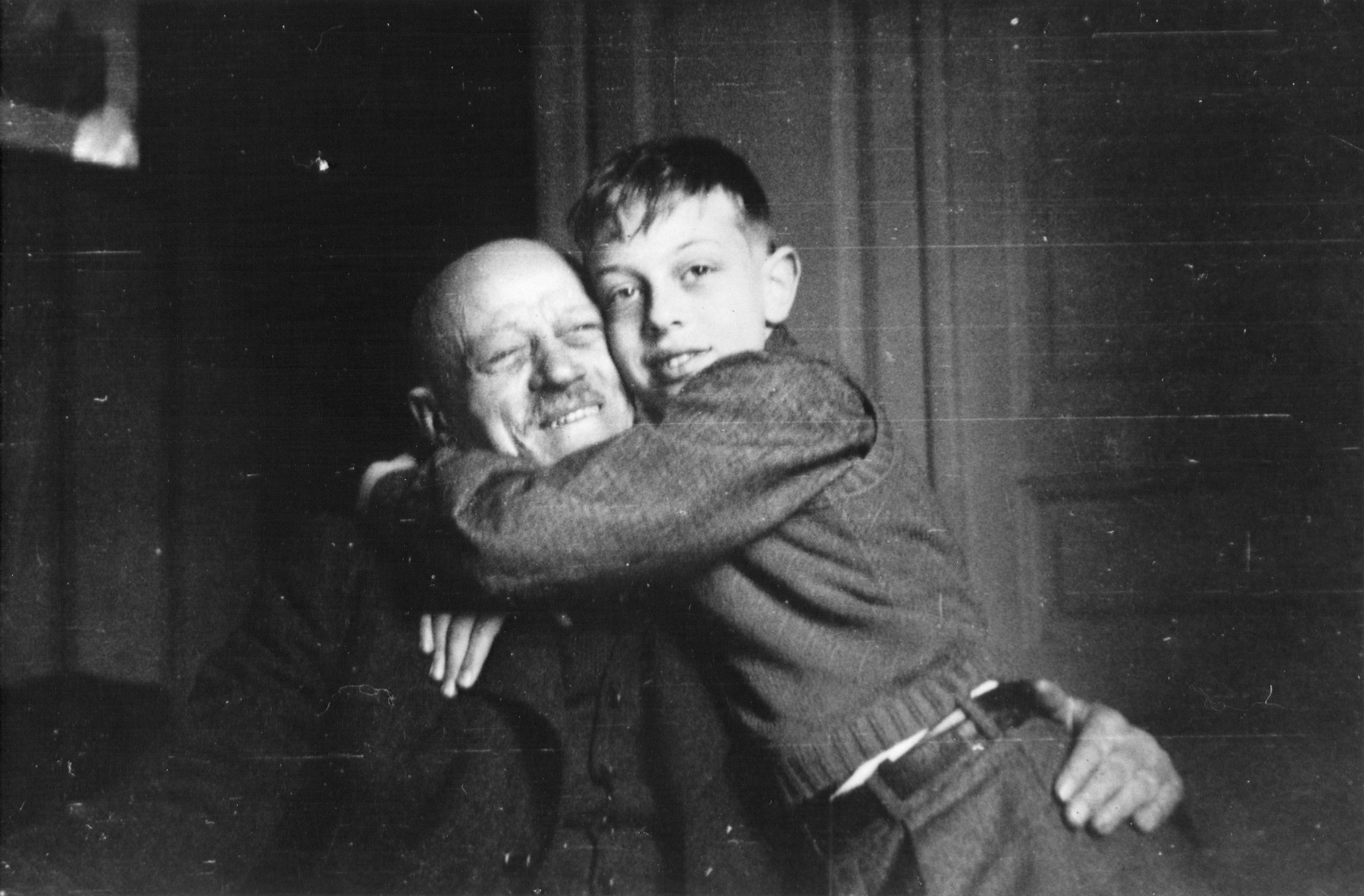Olek gives his [grand]father a bear hug.