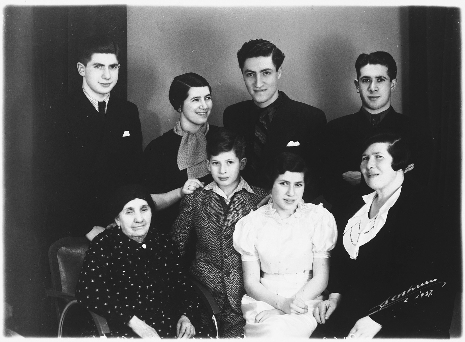 Studio portrait of a Jewish family in Copenhagen taken on their daughter's confirmation.  Pictured in the back row from left to right are: Israel Diament, Kaja Diament, Josef Gendelmann, and Bernhard Diament.  In the front t row from left to right are Chane, Martin, Esther (the confirmand), and Deborah Diament.