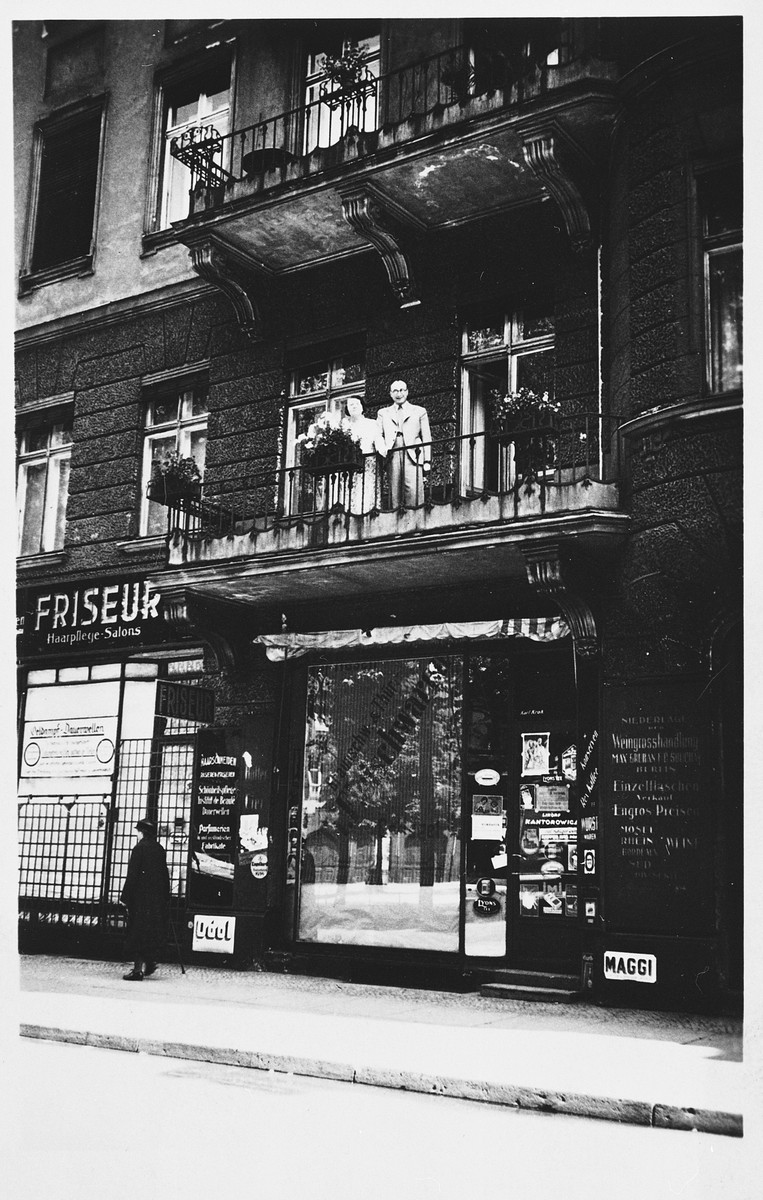 A Jewish doctor and his wife stand on the balcony of their second floor apartment.  Pictured are Hermann and Yetti Meyer.