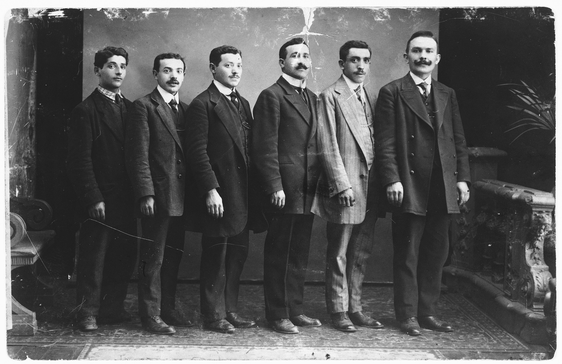 Joseph Diament (second from the right), the owner of a tailor shop in Copenhagen, poses with five of his co-workers.  Also pictured is Nachmendel Lystmann (second from the left).