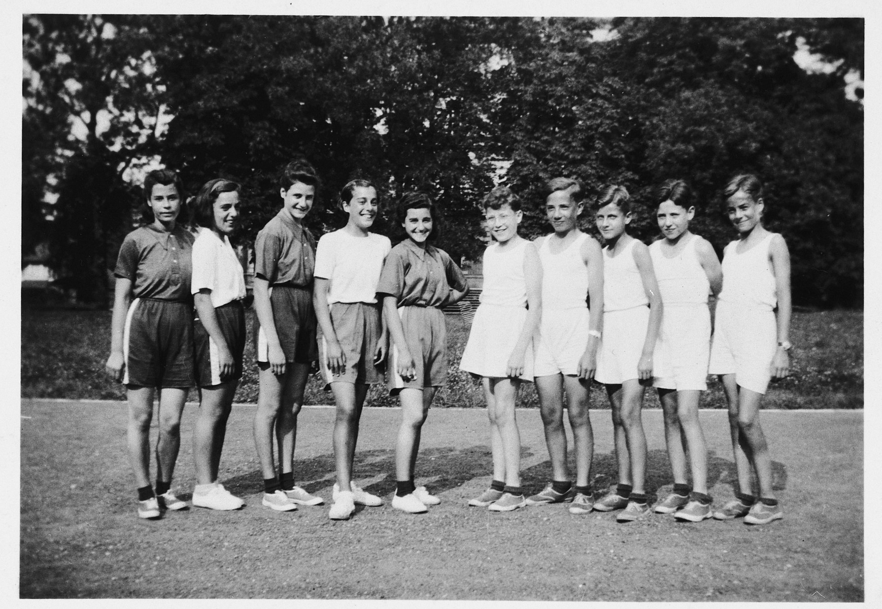 A group of refugee girls from the Russian and Spanish civil wars pose with a group of Jewish refugee boys who came to France on a Kindertransport from Germany at a children's home in Quincy-sous-Senart.  Pictured from left to right are Consuelo Martin, Nati Macaya, Mercedes Martin, Pilar Fernandez, Niaves Martin, Egon Heysmann, Gerhard Rosenzweig, Heinz Rettig, Heinz Levy and Wolfgang Blumenreich.