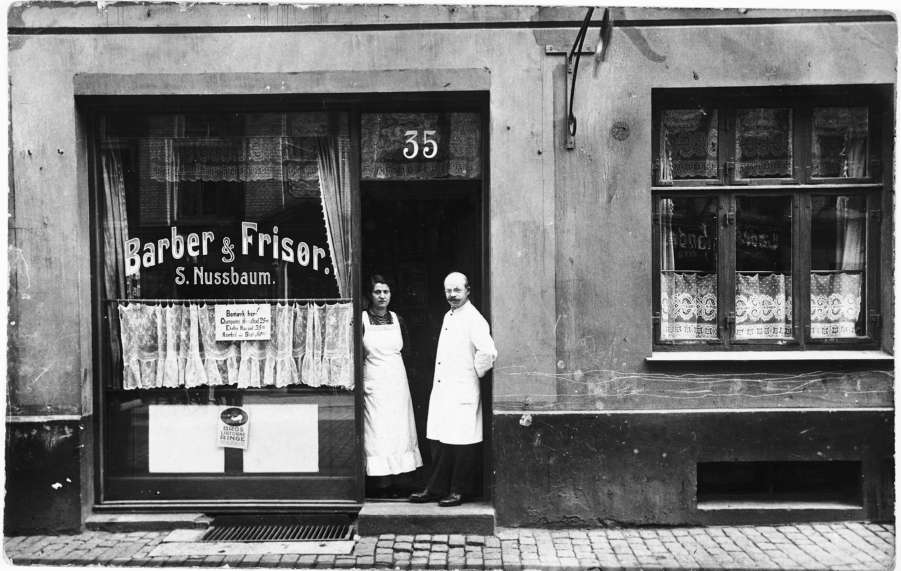 A Jewish couple poses in the doorway of their new barbershop located on the Ochenschlagergade in Copenhagen.  Pictured are Saul and Chane Nussbaum, who live in the same building.