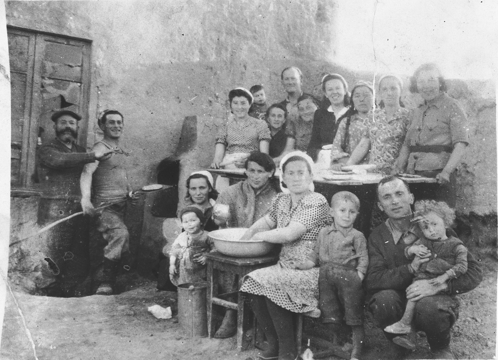 Polish Jews refugees who spent World War II in the Soviet interior, bake matzah for the Passover holiday.  Among those pictured are Joseph Bankir (top row, next to the boy), Israel Bankir (top row, the little boy), Pola Bankir (second row from the top, left), Mojzesz Szczukowski (second from the left, holding the shovel), Hela (Krakower) Szczukowski (front row, left, holding the child, Malka Szczukowski).