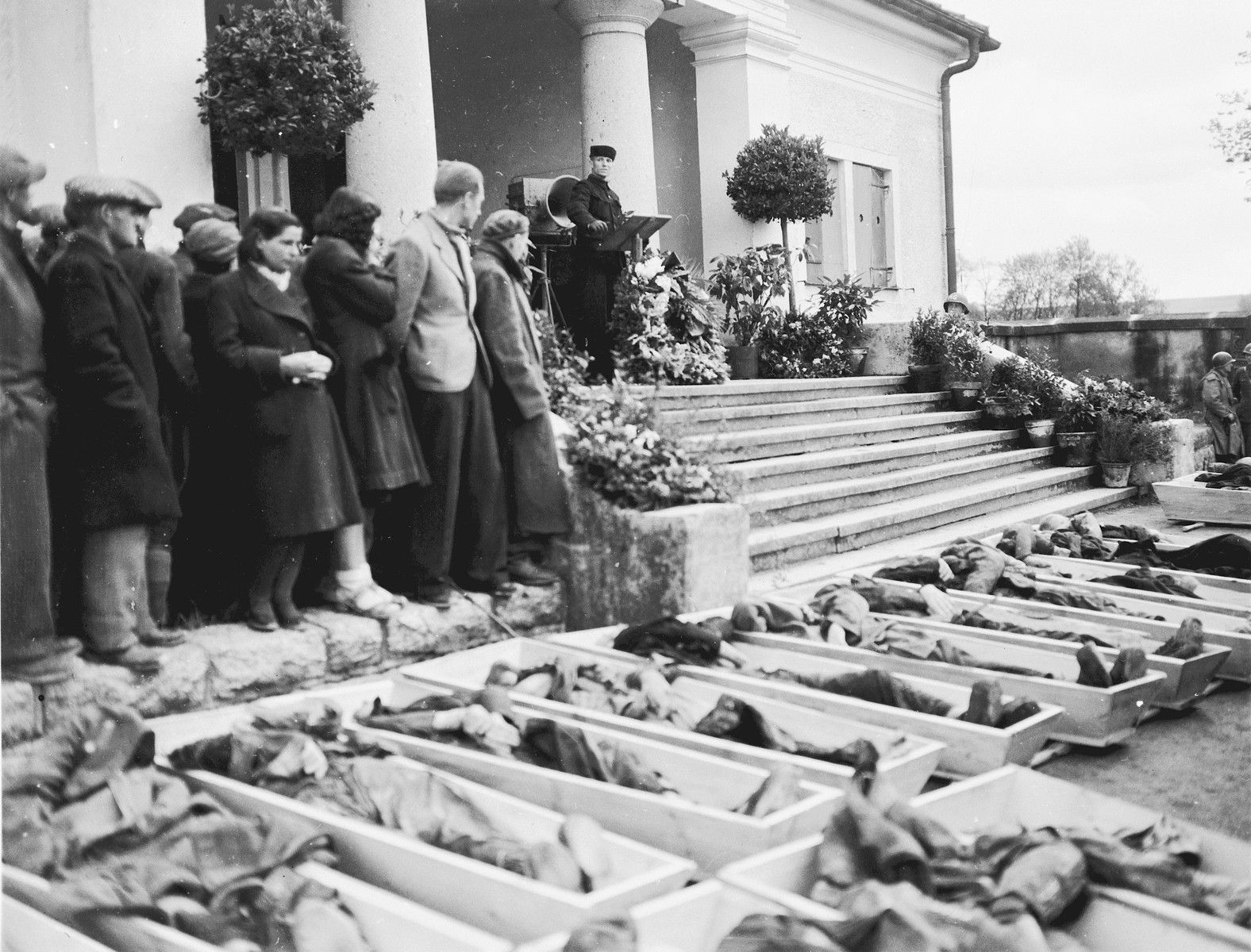 German civilians from Neunburg attend a funeral service for Polish, Hungarian, and Russian Jews found in the forest near their town.    The victims were shot by the SS while on a death march from Flossenbuerg.