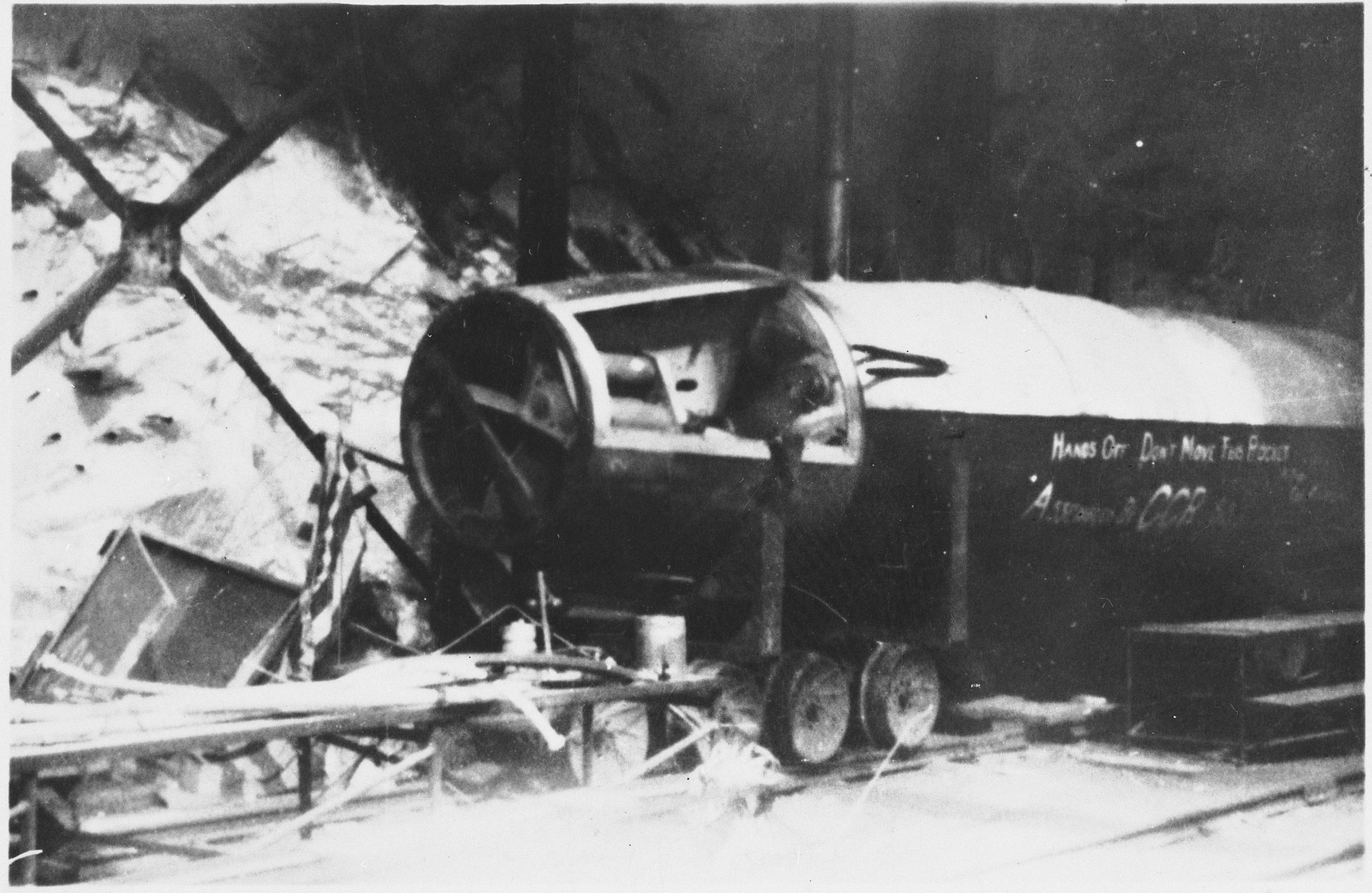 "Interior view of the rocket factory at Dora-Mittelbau.  The original caption reads: ""Front of V-2 less steel nose.  V-2 is approx. 50 ft. long.  Carries 1 ton of T.N.T.  Note train tracks in tunnel.  Regular size trains run thru this tunnel.  They also have living quarters in here."""