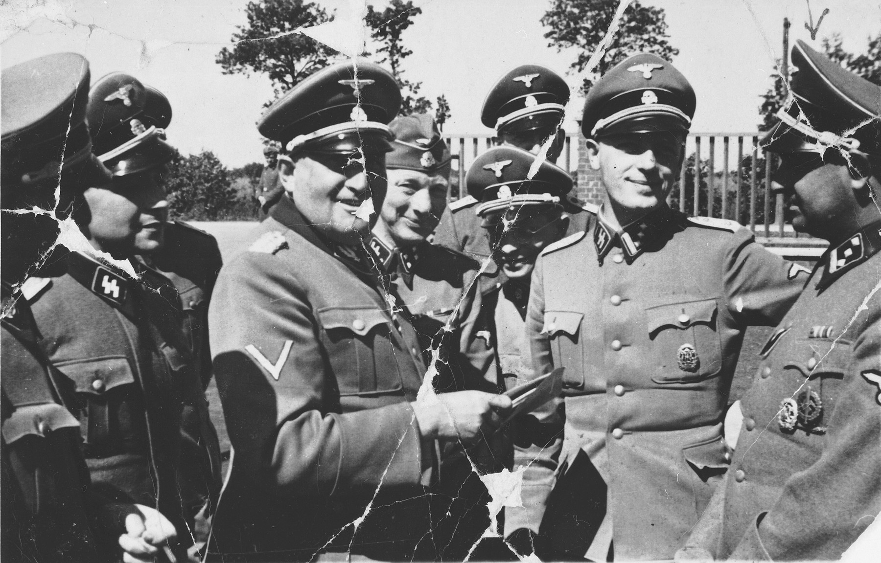 A group of SS officers gather together [probably in Dachau].  Pictured on the far right is Martin Gottfried Weiss.  Richard Gluecks is in the center facing to the right.