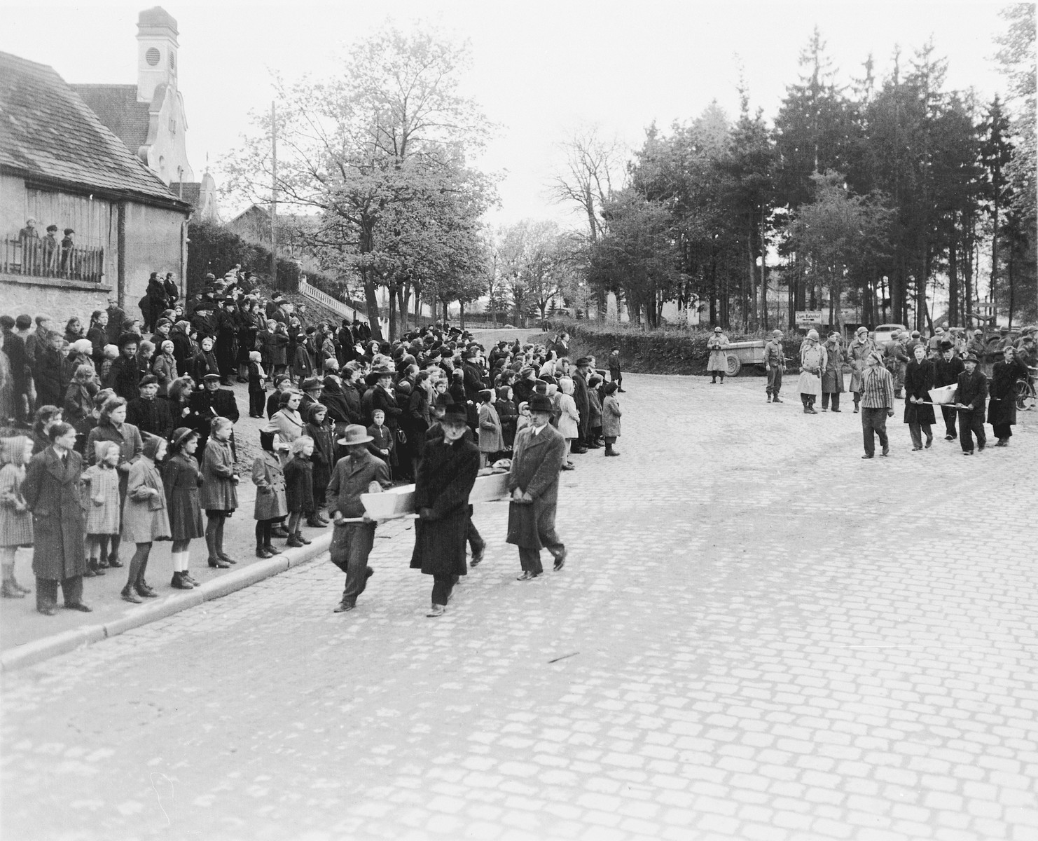 The townspeople of Neunburg vom Wald line the streets and watch as their fellow townspeople transport corpses found in the nearby forest to the town cemetery for proper burial.    The victims were Polish, Hungarian, and Russian Jews shot near Neunburg while on a death march from Flossenbuerg.