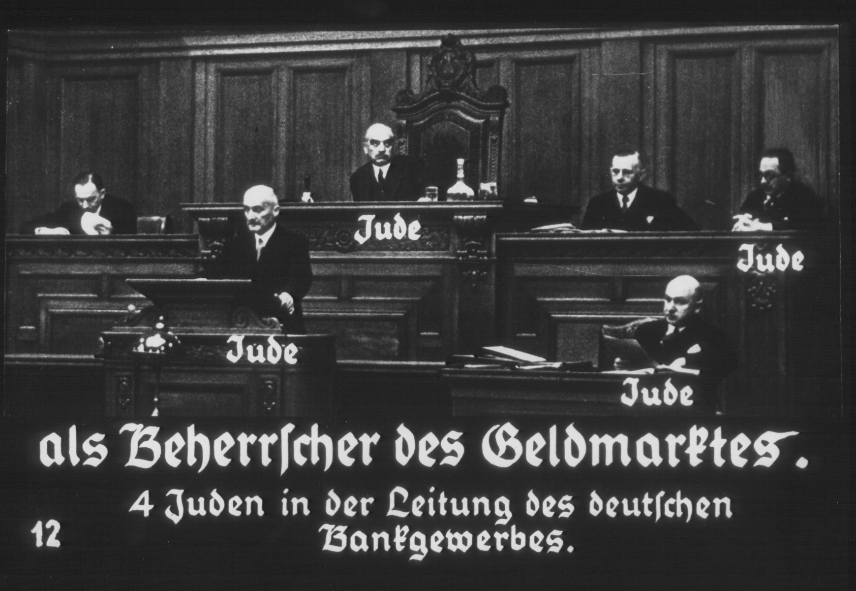 "Propaganda slide entitled ""Jews as rulers of the money markets.  4 Jews in the directorate of the German banking industry.""   Chairman Georg Adolf Solmssen delivers a speech from the podium.  Above him, from left to right are: Walther Frisch (Dresdner Bank); Max Warburg (vice-chairman of the Zentralverband); Otto Bernstein (general secretary of the Zentralverband); and Eduard von Eichborn.  Below Eichborn sits Dr. Fraenkel."