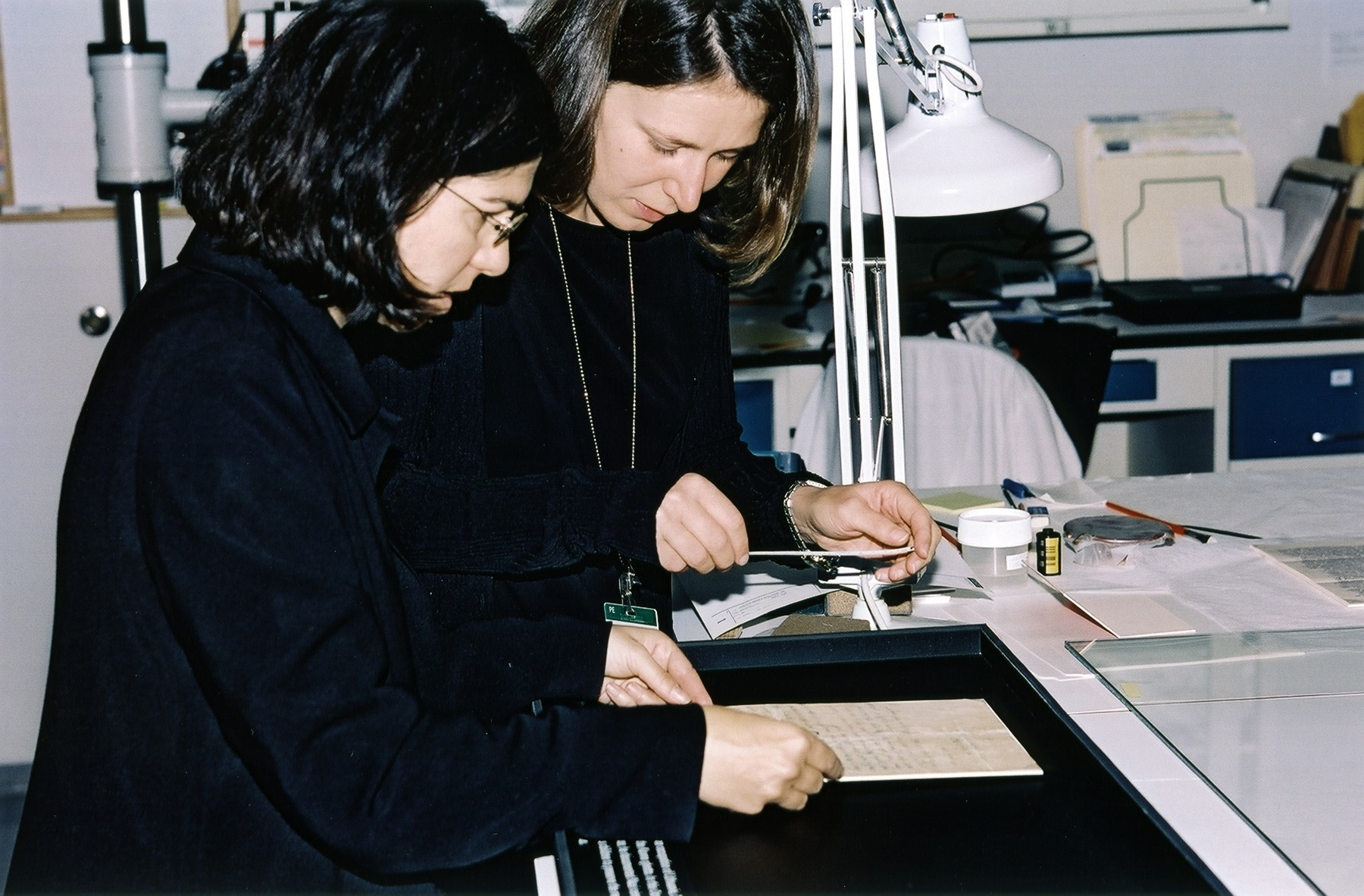 Photo conservator Emily Jacobson and Permanent Exhibition Coordinator Kathleen Mulvaney measure an artifact in the Museum's conservation lab before it is installed in the Permanent Exhibition as part of a regular rotation plan.  The document pictured is the ethical will of Elkhanan Elkes, the chairman of the Kovno ghetto Jewish Council.