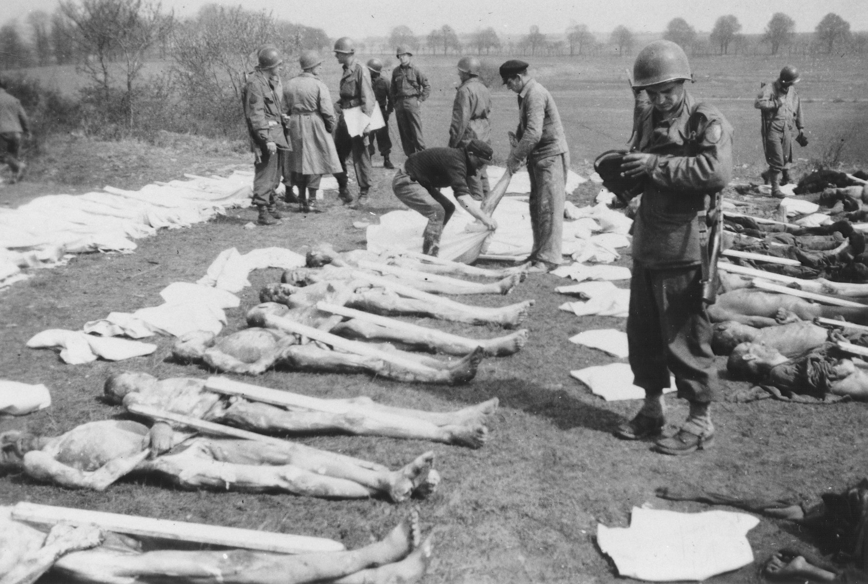 American soldiers supervise German civilians who they have forced to prepare victim corpses for burial in the Ohrdruf concentration camp.
