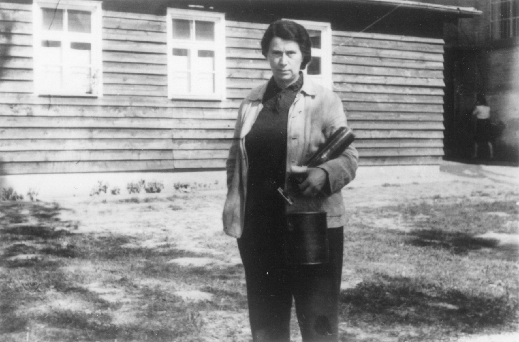 Ida Brauer poses with a metal can in front of the delousing unit where she worked.