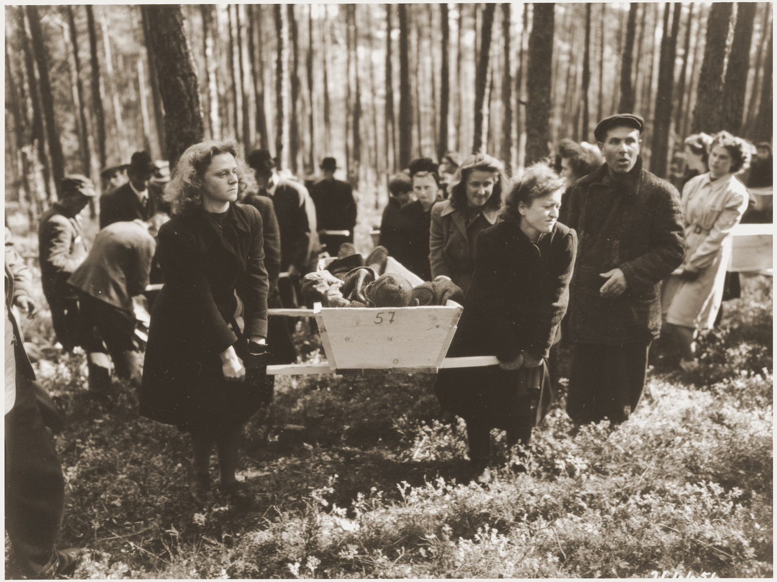 "German women transport a corpse found in the woods near Neunburg vorm Wald to the town cemetery for proper burial.    The victims were Polish, Hungarian, and Russian Jews shot near Neunburg while on a death march from Flossenbuerg.   The original caption reads, ""On orders of Third U.S. Army officers, German, civilians of Neunburg and surrounding towns were forced to provide respectable buial for 120 victims of SS troop killings.  The victims - Polish and Russian slave laborers - were murdered by the Nazis in a wooded region of the area during the advance of American forces.  Some of the victims were shot, others were found with their skulls crushed."""