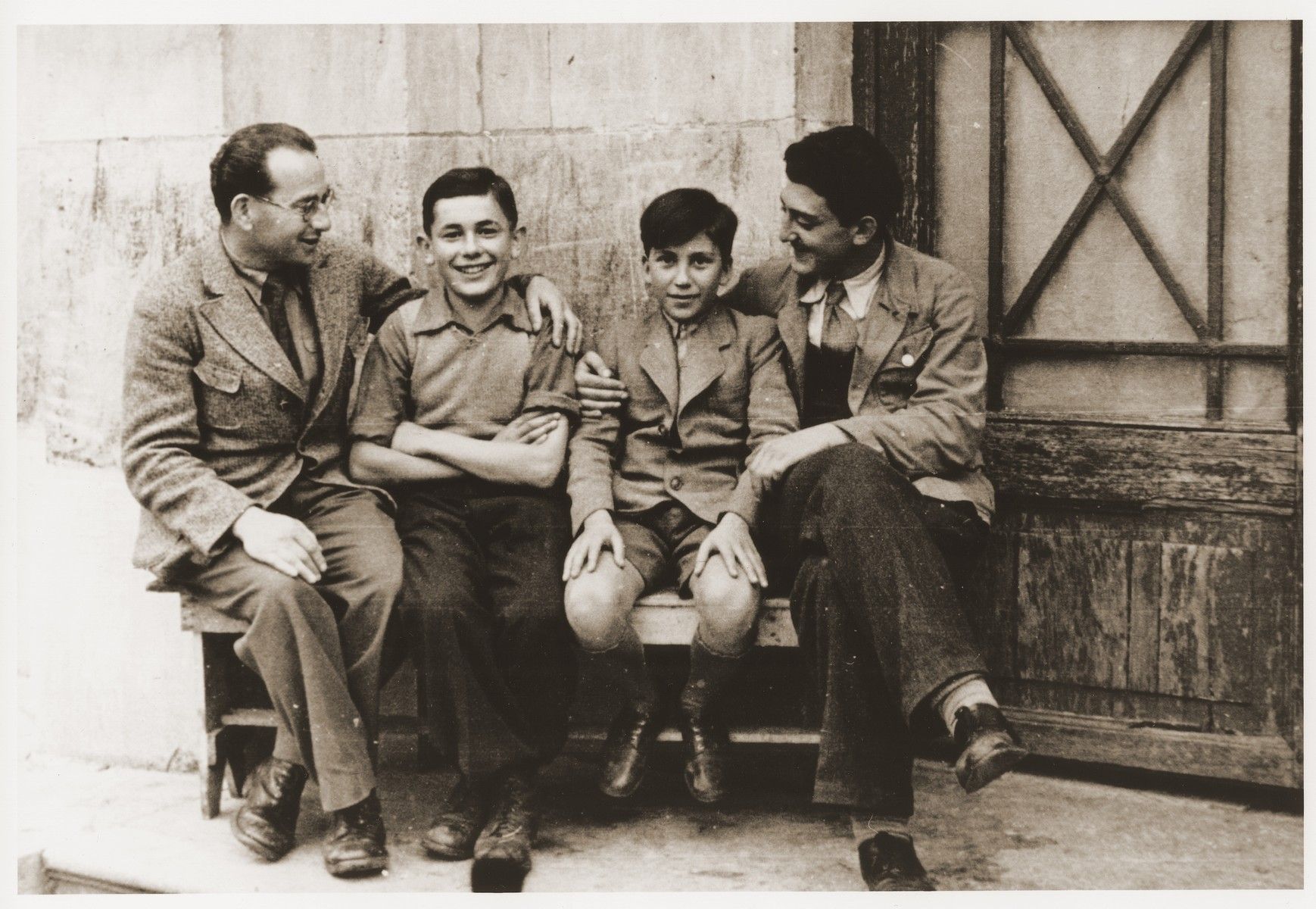 Two Jewish boys sit on a bench with their counselors at the Rothschild's Château Ferrière, where they are attending a summer camp sponsored by the OSE (Oeuvre de secours aux Enfants).   Pictured from left to right are Manfred Reingewitz, Romek Wajsman, Salek Finkelstein and Ralph Lewin.