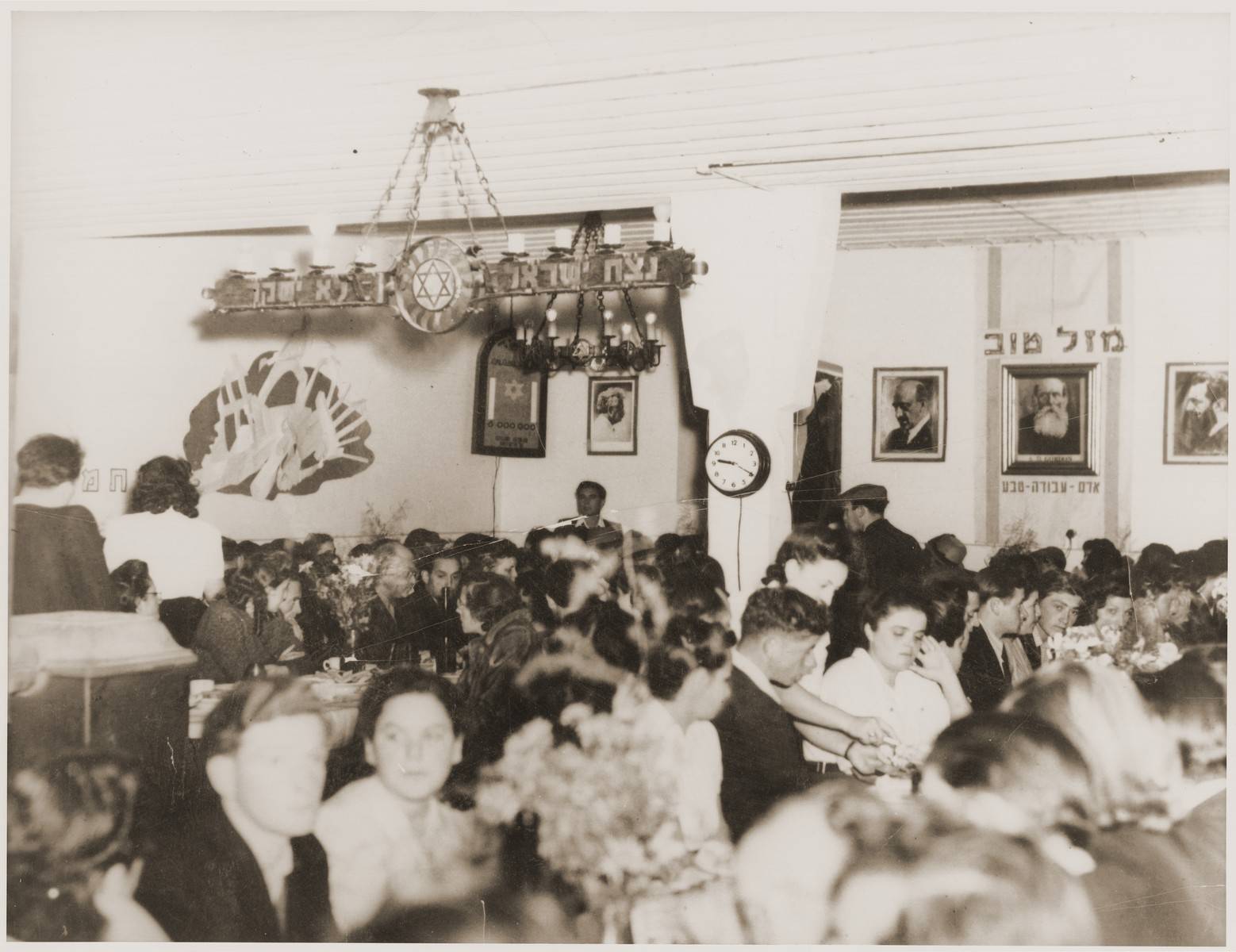 Members of the Kibbutz Nili hachshara (Zionist collective) in Pleikershof, Germany are gathered in the dining hall for a festive meal.   The room is decorated with portraits of Zionist leaders, including Herzl, Weizmann and A.D. Gordon, and the kibbutz motto.