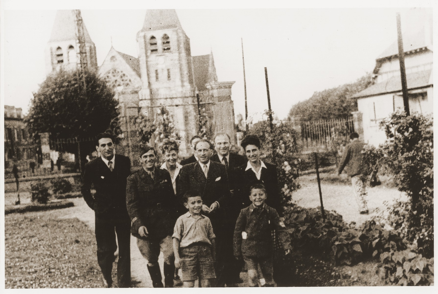 Representatives of the OSE (Oeuvre de Secours aux Enfants) pose with two members of the Buchenwald children's transport in the town square of Ecouis.    Pictured in the front from left to right are David Perelmutter and Yisrael Meir (Lulek) Lau. The man in uniform is Colonel Rozen.  Gaby (Nini) Wolff is on the far right.