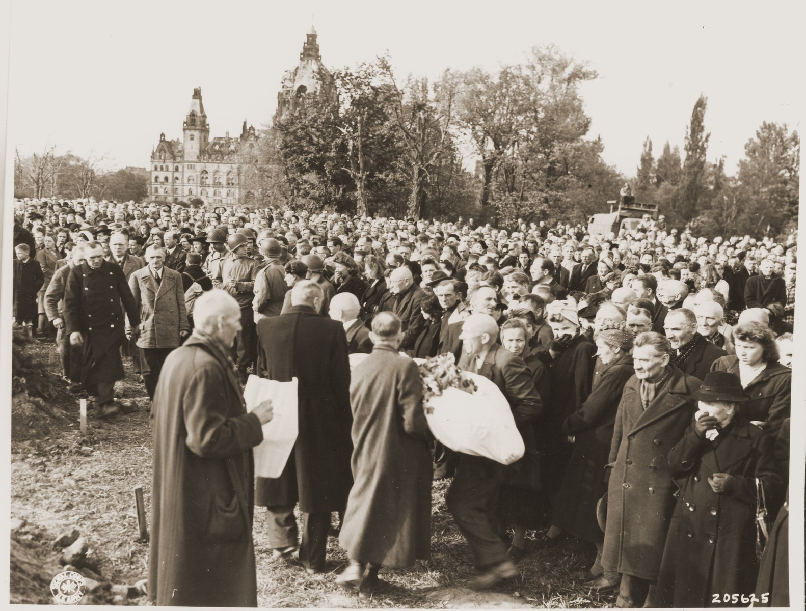 German civilians carry the body of one of 200 Russian prisoners, exhumed from a mass grave in Wuelfel, to a new grave near Hanover City Hall.  On April 8, 1945, 200 Red Army officers and other prisoners of war were sent on a death march from the Liebenau labor camp, 50 kilometers NW of Hanover, where the prisoners worked in a munitions factory.  As they reached Wuelfel, a suburb of Hanover, the SS guards ordered 25 prisoners, including one woman, to dig a large grave.  While this was being done, a prisoner killed a guard with a shovel and was able to escape to the woods nearby.  From there he heard the shots as the remaining prisoners were killed and buried in the grave.  Several weeks later, as American troops swept through the area, the mass grave was discovered.  On May 2, the 35th Division of the U.S. Ninth Army gathered townspeople from Wuelfel and forced them to exhume the grave, wrap the bodies in sheets, and rebury them near the Hanover City Hall.  Before reburial, many of the victims were identified by friends and relatives remaining in the area.
