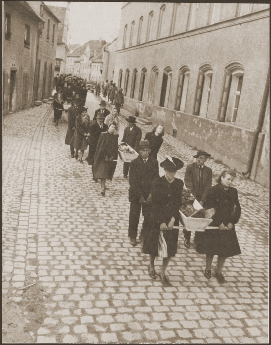 "Under the supervision of American soldiers, German civilians from Neunburg vorm Wald carry wooden coffins containing the bodies of Hungarian, Russian and Polish Jews to the town cemetery for proper burial.    The victims were found in the woods near the town where they were shot by the SS while on a death march from Flossenbuerg.  Original caption reads, ""Civilians of the city of Nurnburg at the task of carrying the bodies of the slave laborers over the mile and a half stretch to the burial grounds."" [sic]  Original Signal Corps caption reads, ""NEUNBURG ATROCITY VICTIMS BURIED.  On orders of Third U.S. Army  officers, German civilians gave a decent burial to 120 Neunburg concentration camp inmates who were murdered by German SS troops in a wooded area one mile from the City of Neunburg before the town was taken by advancing Third Army soldiers.  The victims, Polish and Russian slave laborers, were murdered in several different ways, the most common being by a skull-crushing blow from a blunt instrument.  Some were also shot in the head.  Some of the prisoners were originally from Weimar and several other concentration camps.  Before the atrocity was carried out, German civilians of Neunburg said SS troops ordered citizens of the town into their homes and threatened them with death if they ventured out.  After the Americans took over the area and discovered the crime, they ordered the civilians to carry the corpses from the woodland shooting site into the city for burial in a cemetery.  PNA                                                            EA 64879  THIS PHOTO SHOWS:  German women and men of Neunburg bear the bodies of the victims from the death site to burial in the town cemetery.  U.S. Signal Corps Photo ETO-HQ-45-34602. SERVICED BY LONDON OWI TO ILST B CERTIFIED AS PASSED BY SHAEF CENSOR"