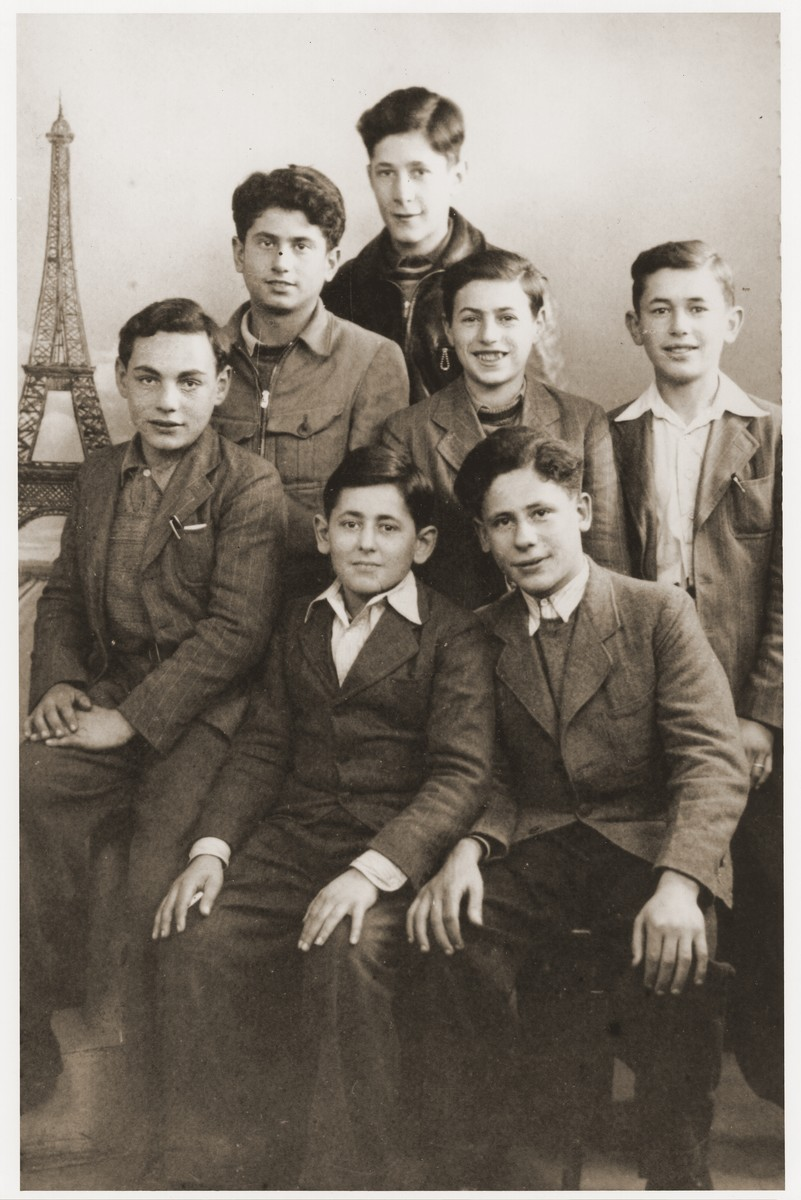 Group portrait portrait of Jewish children against a backdrop of the Eiffel Tower.    The children are residents of the Le Vésinet children's home, sponsored by the OSE (Oeuvre de secours aux Enfants).    Pictured in the front from left to right are Joseph Fachler, Abram Chapnick and Herchel Unger.  In the middle row are Leon Friedman, Salek Sandowski and Romek Wajsman.  Standing behind is Marek Lozinski (b. Lodz, 1927).