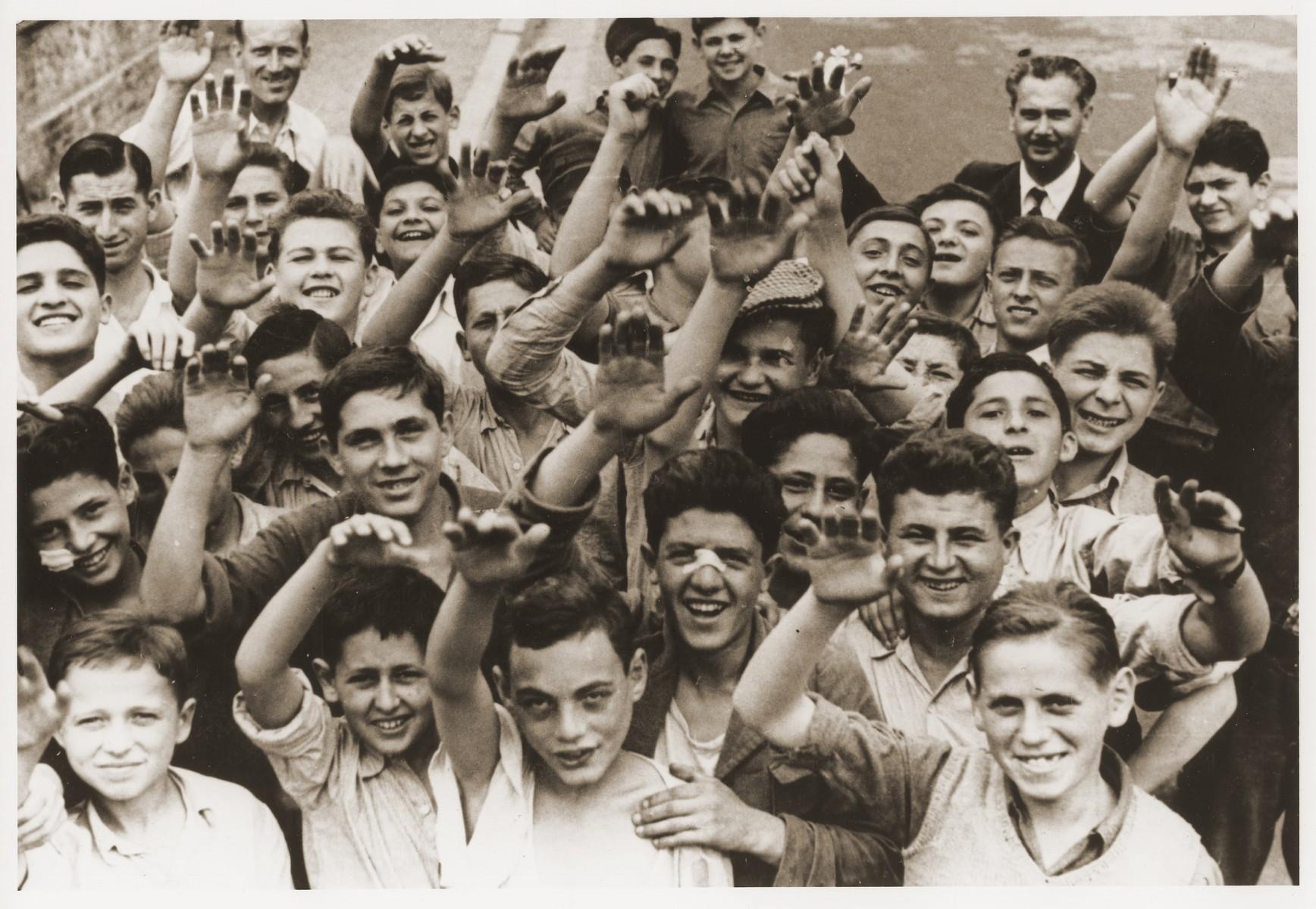 Jewish DP youth who were members of the Buchenwald children's transport wave to the camera at the Ecouis children's home.  Among those pictured are Zysio Abramovicz, Abram Czapnik, Albert Dymant, Joseph Fachler, Léon Frydman, Moritz Freilich, Idek Goldmann, Lejzor Grunberg, Israel Grojsman, Jakob Kapelusz, Mayer Kilsztok, Léon Lewkowicz and Hersch Unger.  [See enclosed sheet for precise identifications.]