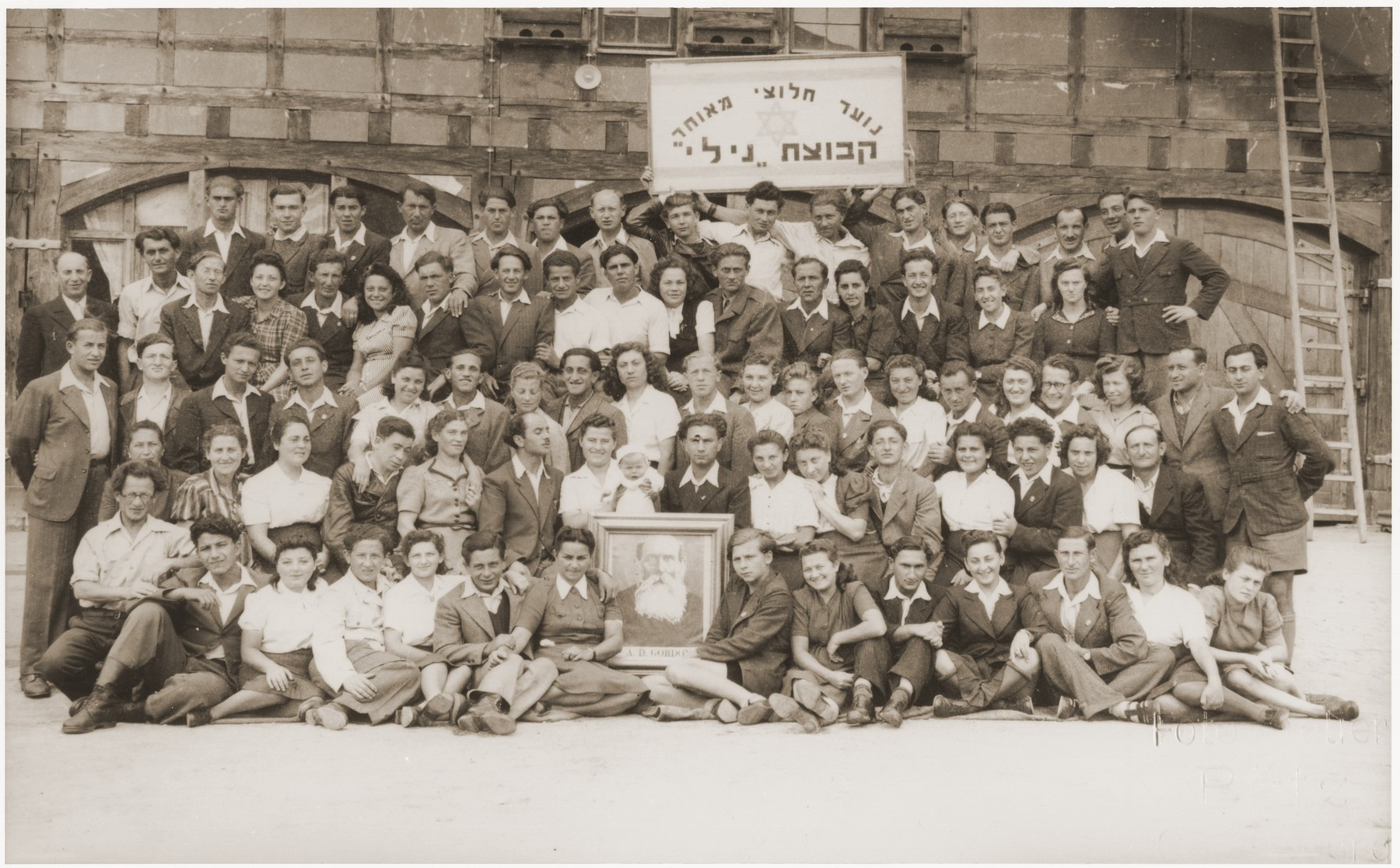 Group portrait of members of the Kibbutz Nili hachshara (Zionist collective) in Pleikershof, Germany  Those in the front row hold a protrait of labor Zionist idealogue A. D. Gordon.  Sitting directly behind the portrait are Noach and Sara (Feldberg) Miedzinski with their infant daughter Nili Ruchana.
